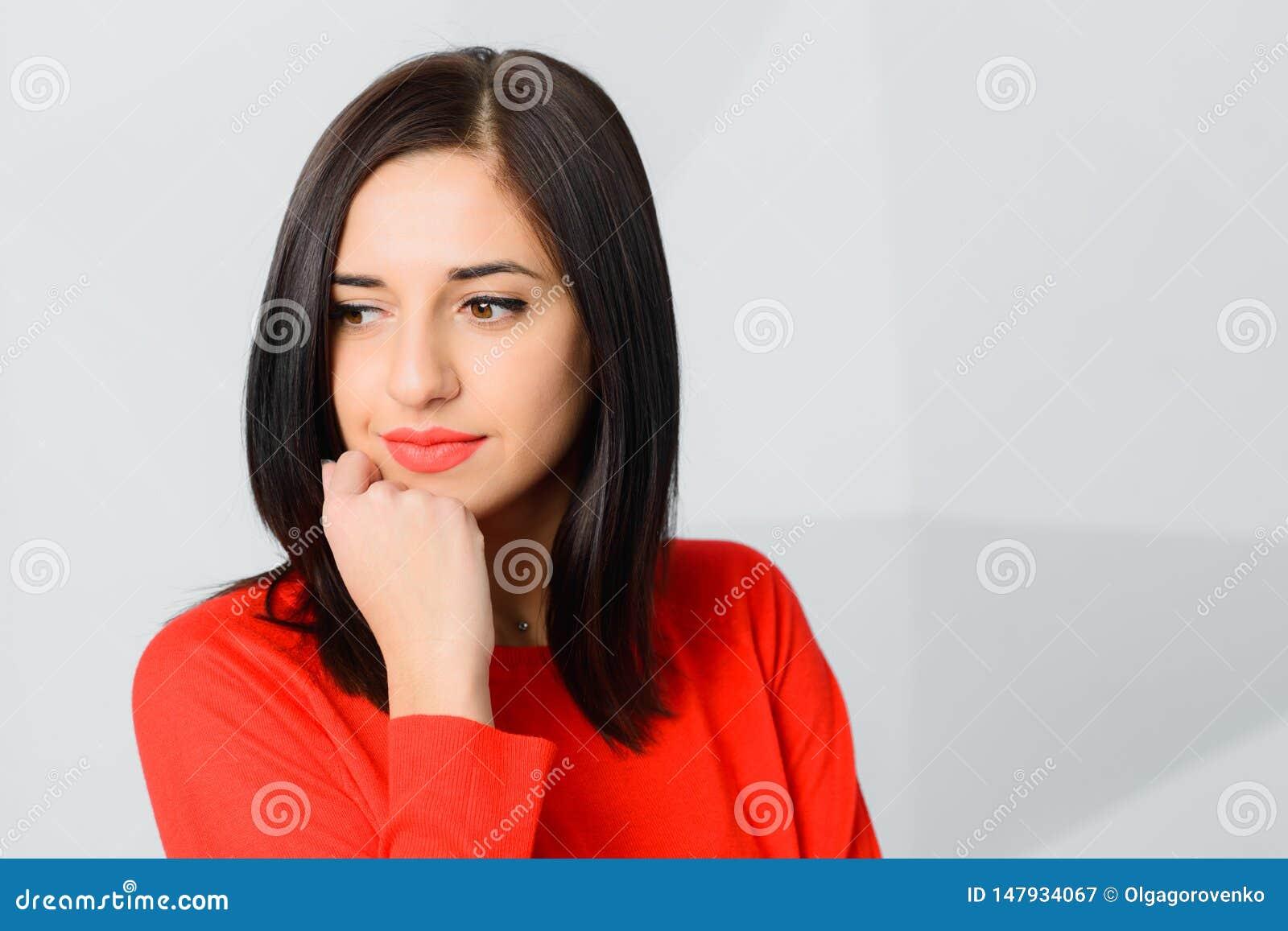 Vermelho vestindo da jovem mulher smily pensativa moreno