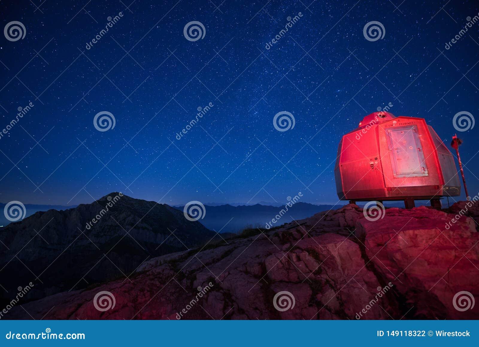Vermelhos iluminados acampam nas montanhas altas sob um c?u estrelado bonito