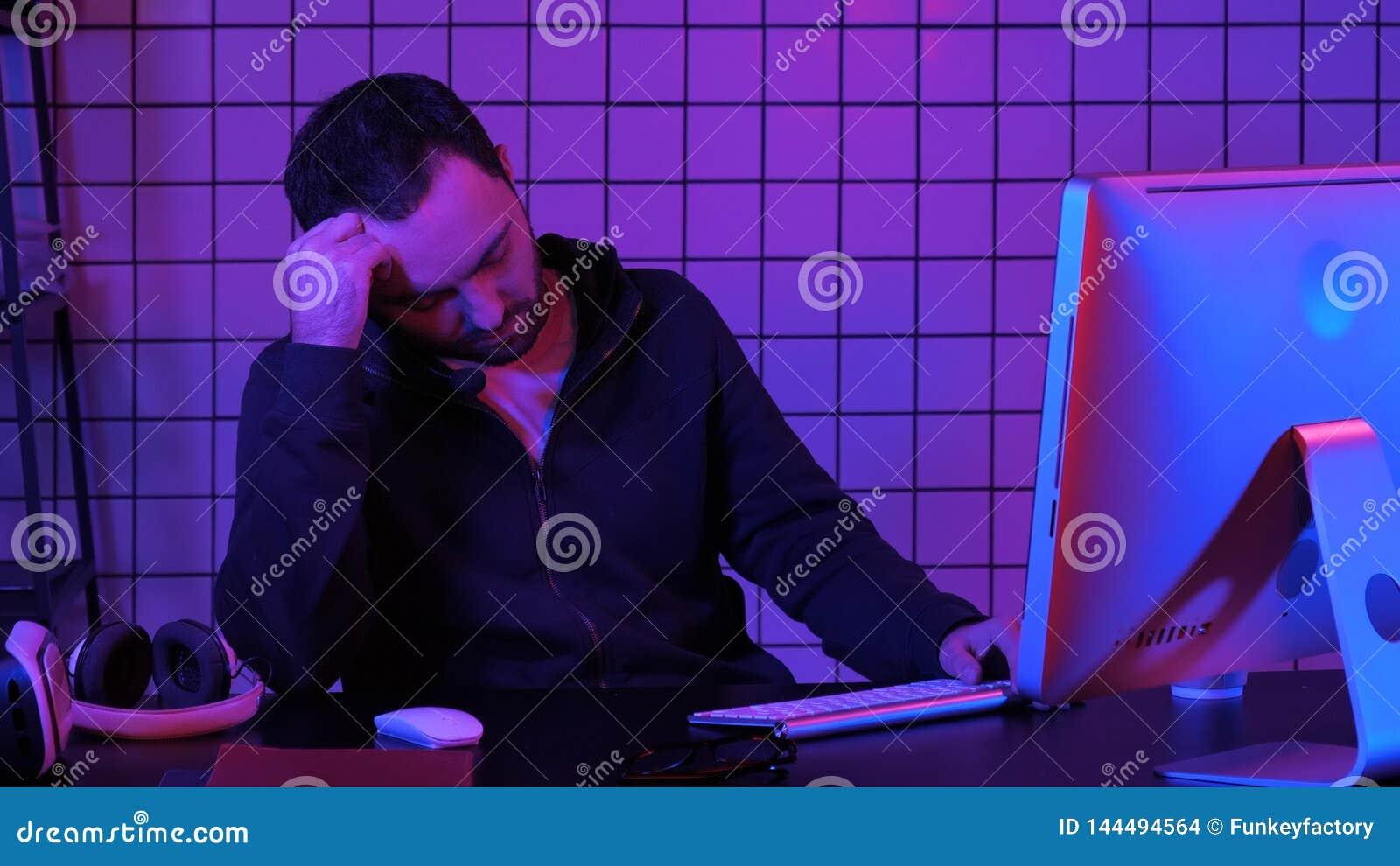 Vermoeide hakkerslaap dichtbij computer terwijl computerverwerking