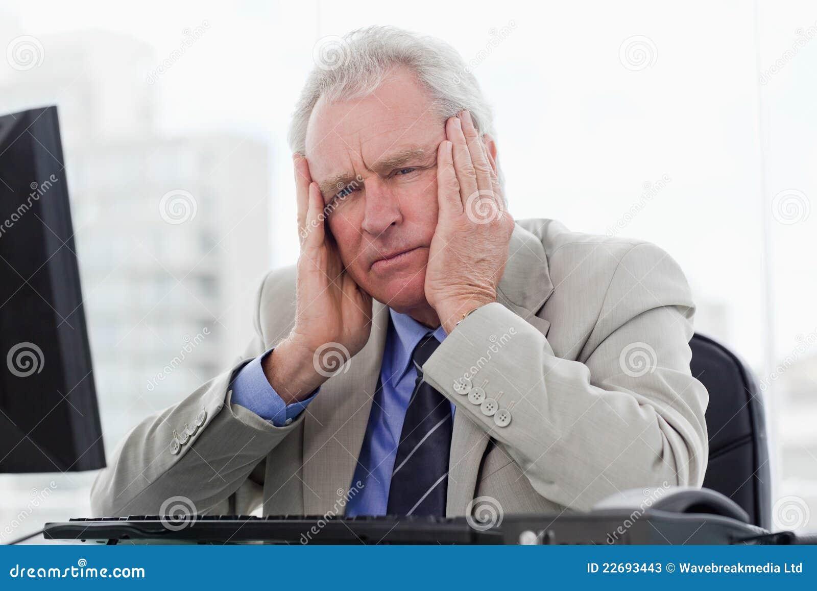 Vermoeide hogere manager die met een monitor werkt