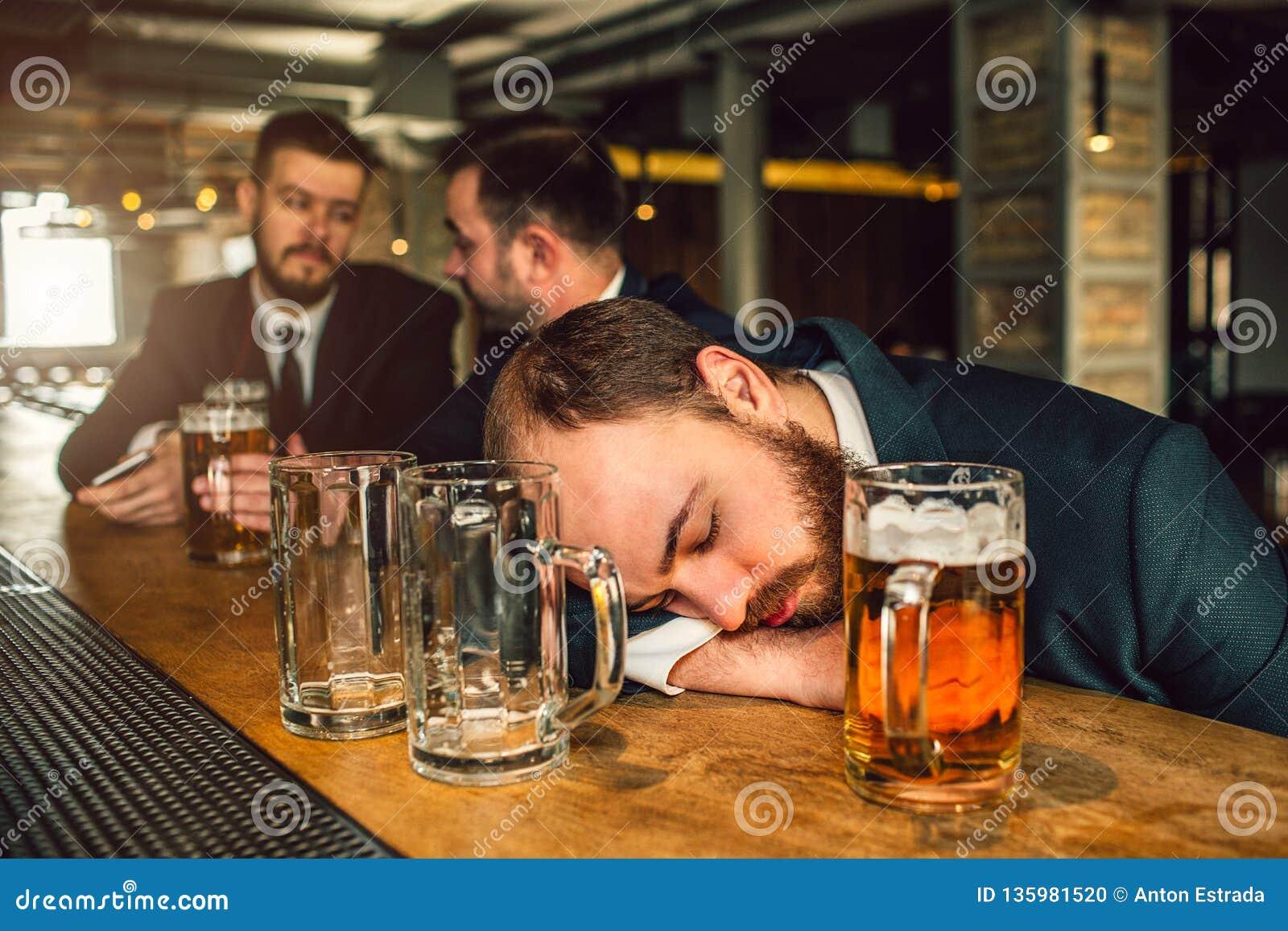 Vermoeide jonge mens in kostuumslaap op barteller hij is gedronken er zijn twee lege mokken en één hoogtepunt met bier Andere twe