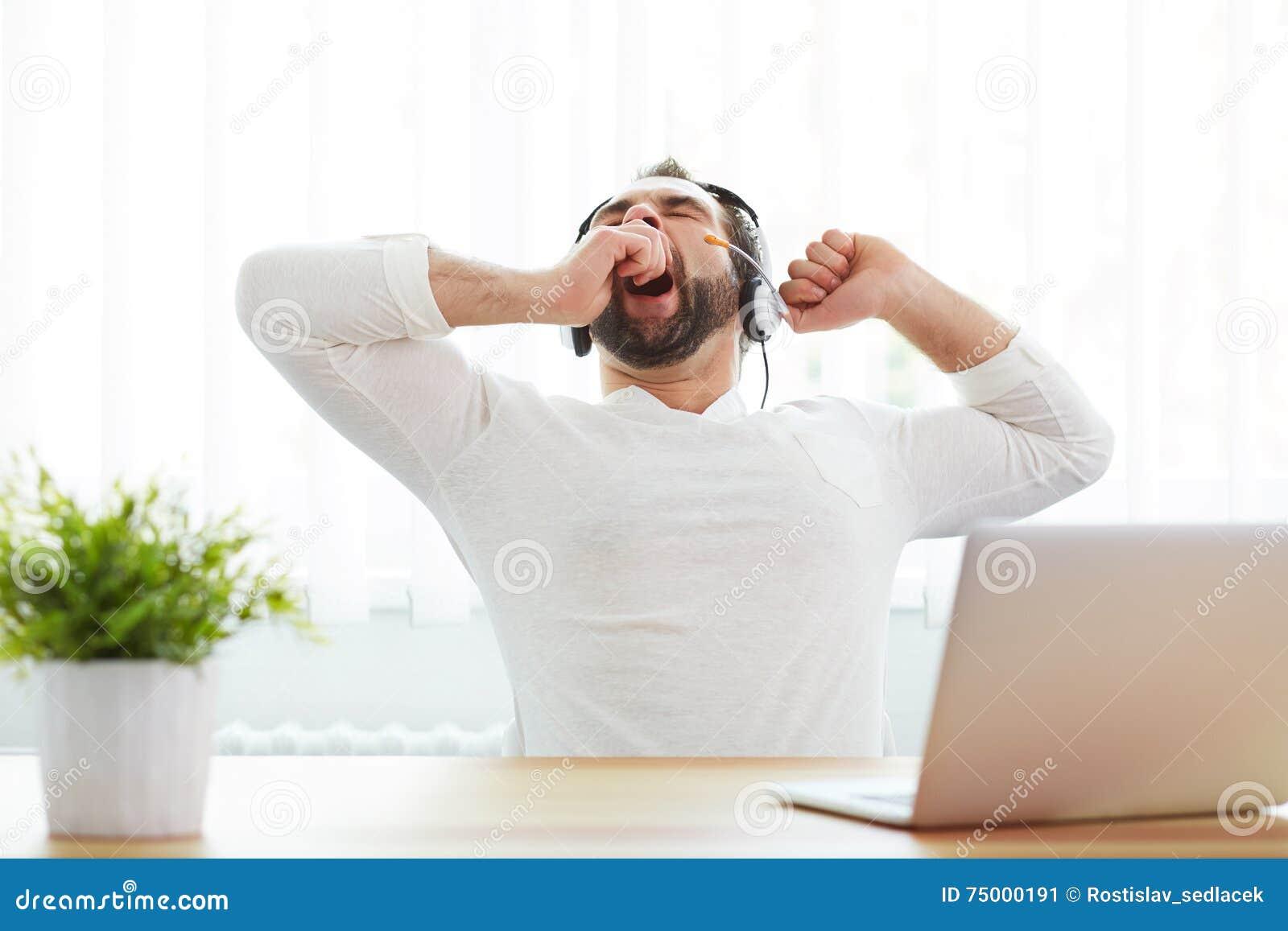 Vermoeide mannelijke exploitant met hoofdtelefoon