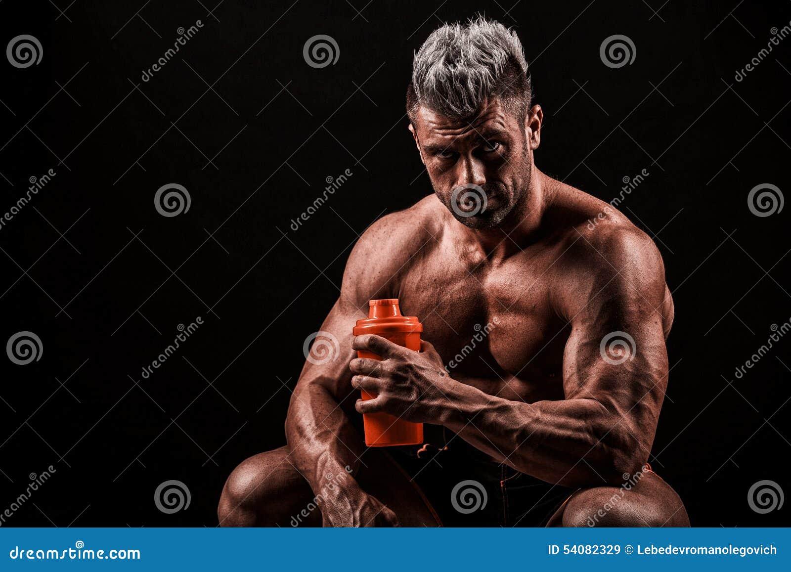 Vermoeide mens die na opleiding rust, die fles in hand houdt