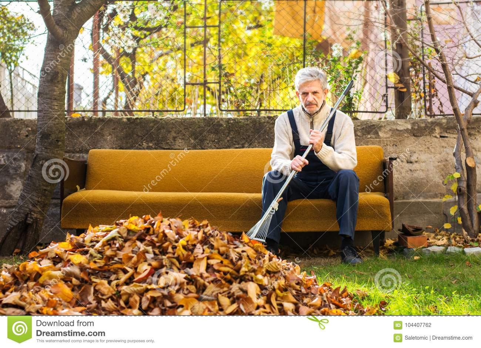 Vermoeide mens die rust van het schoonmaken van gevallen de herfstbladeren nemen in