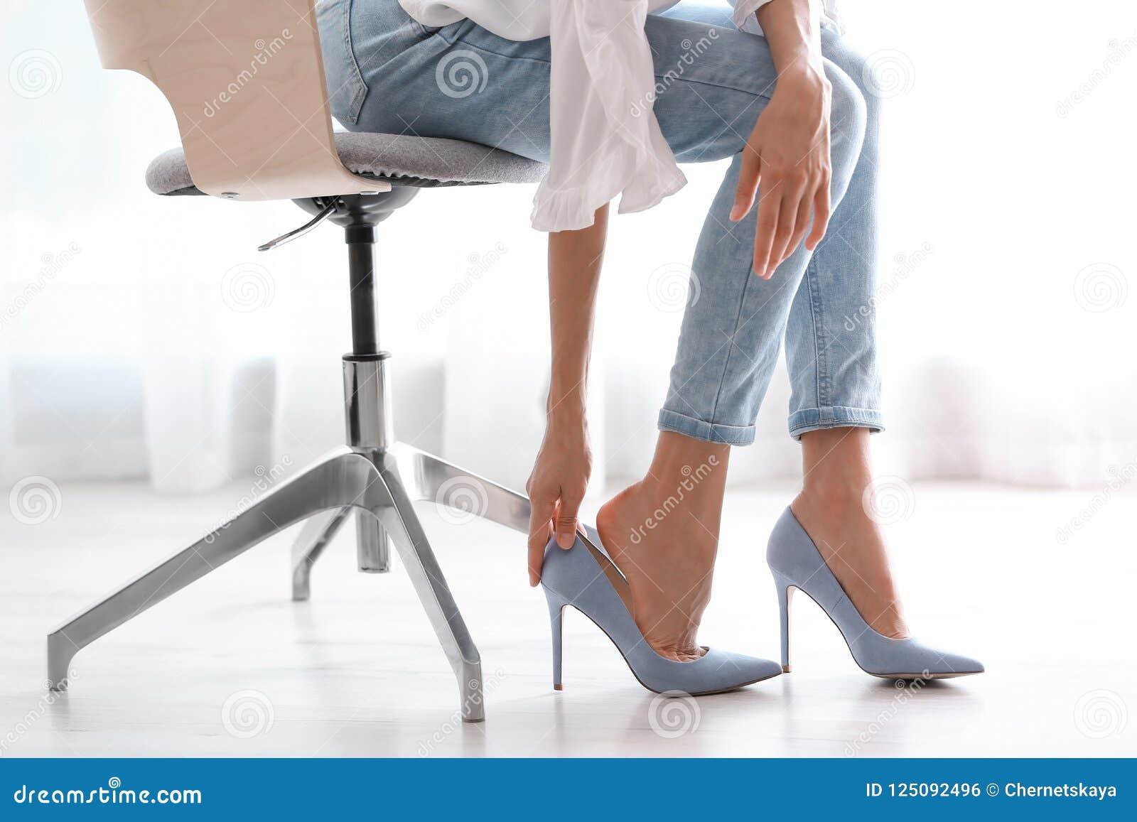 Vermoeide vrouw die schoenen opstijgen op kantoor