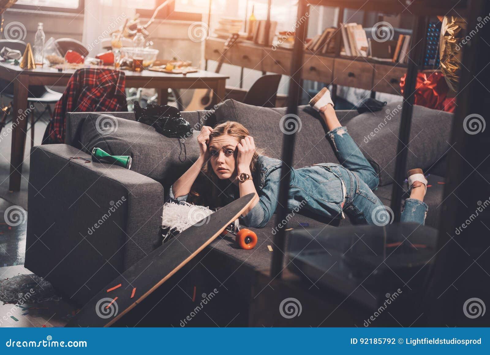 Vermoeide vrouw met kater die op laag na partij liggen