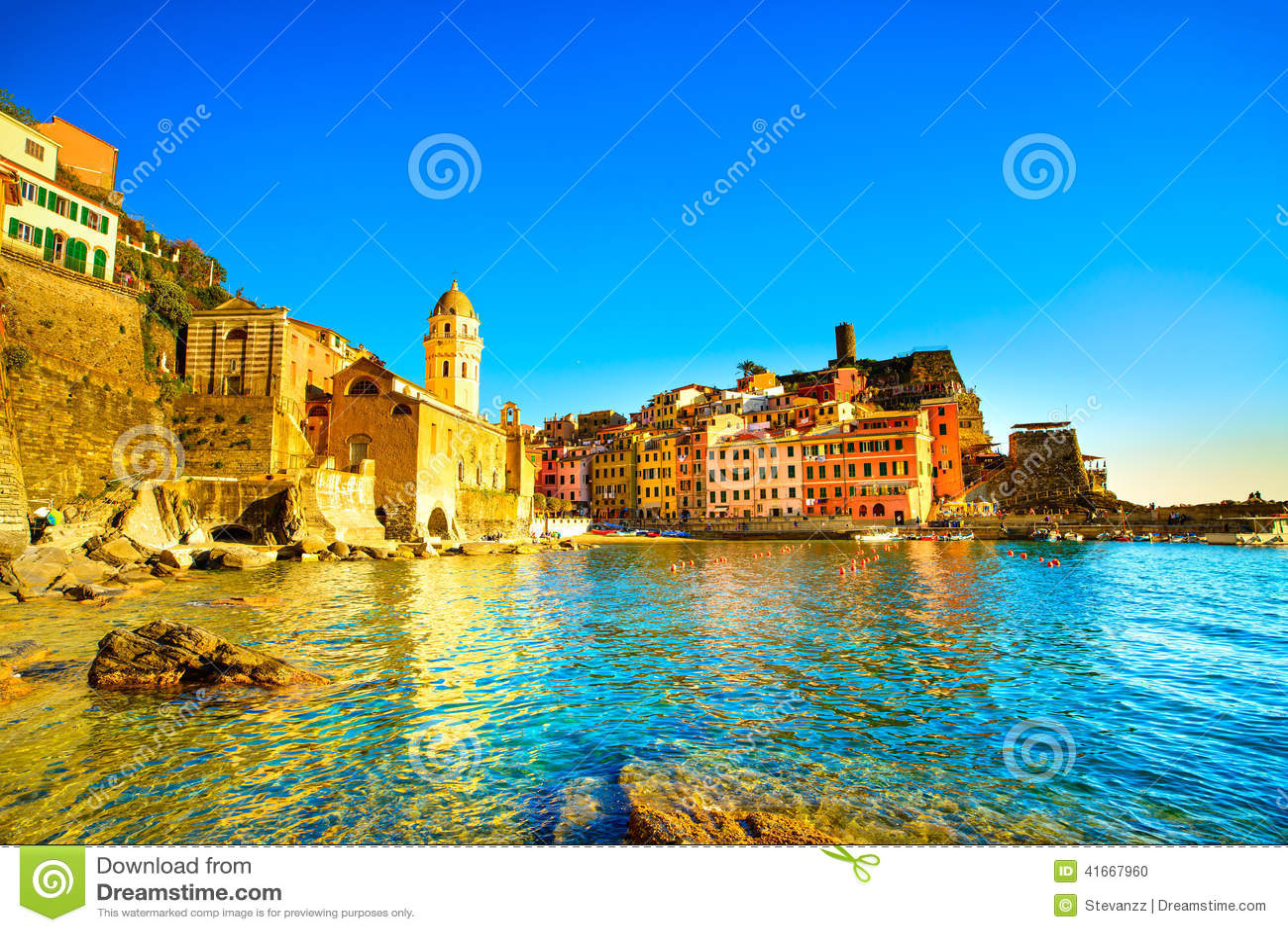 Vernazza village, church, rocks and sea harbor on sunset. Cinque