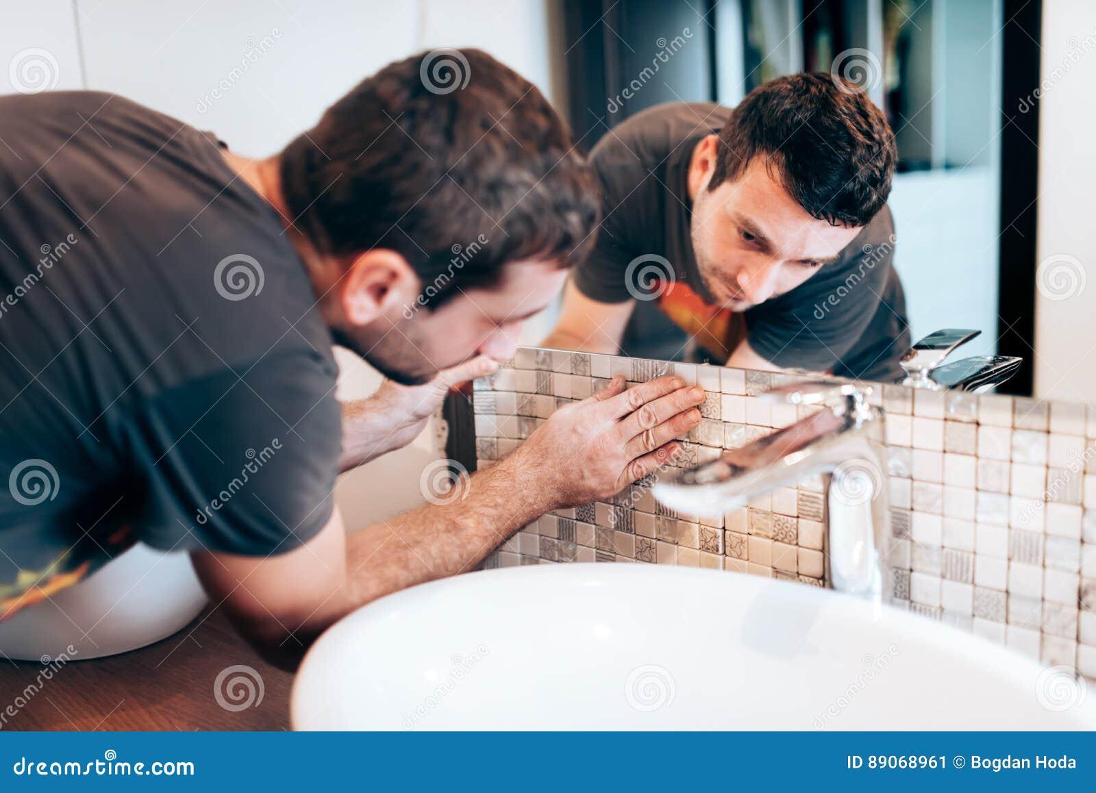 Vernieuwingsdetails Bouwdetails met manusje van alles of arbeider die mozaïekkeramische tegels op badkamersmuren toevoegen