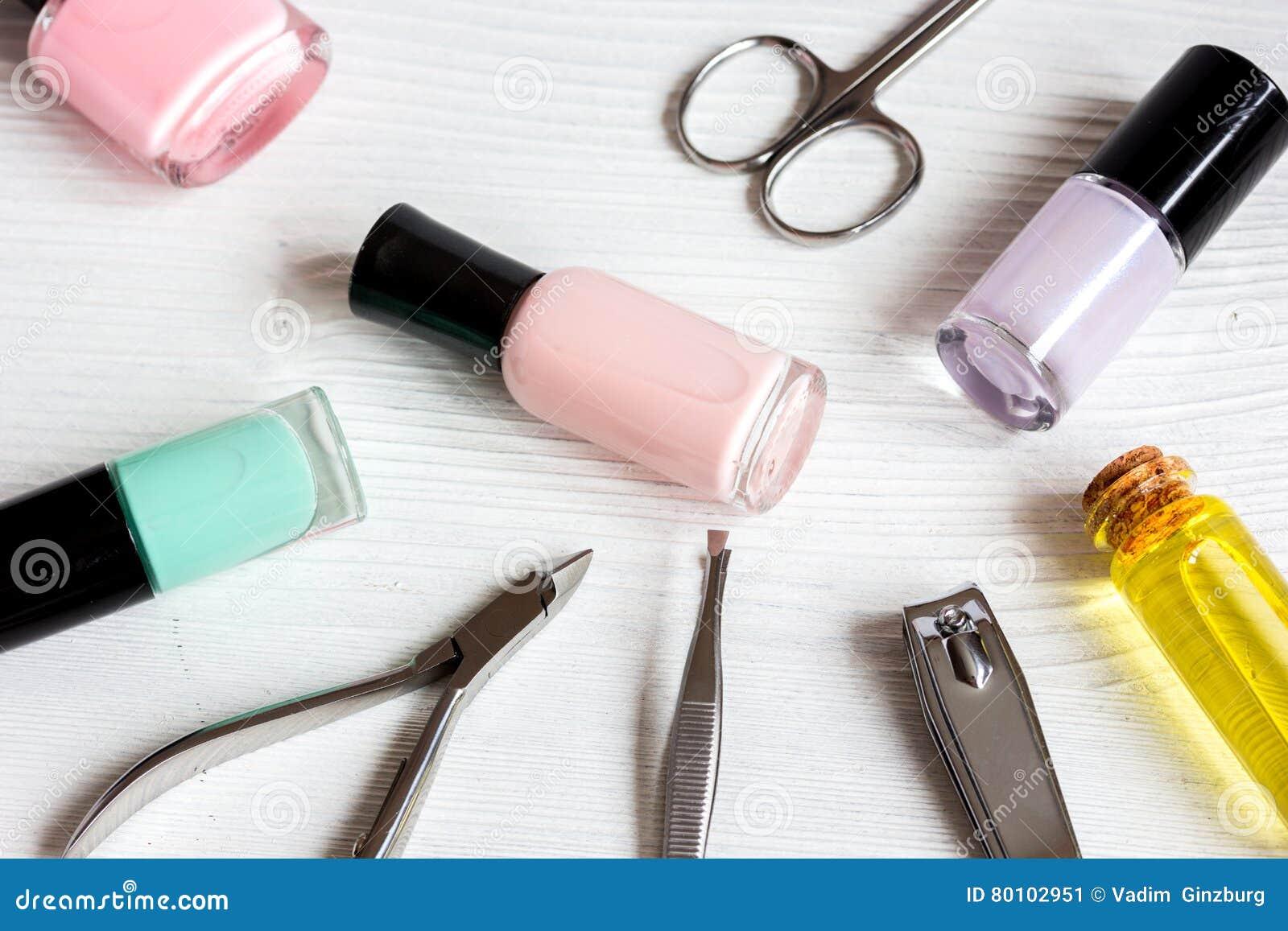 Verniz para as unhas, óleo da cutícula e grupo de tratamento de mãos no fundo de madeira