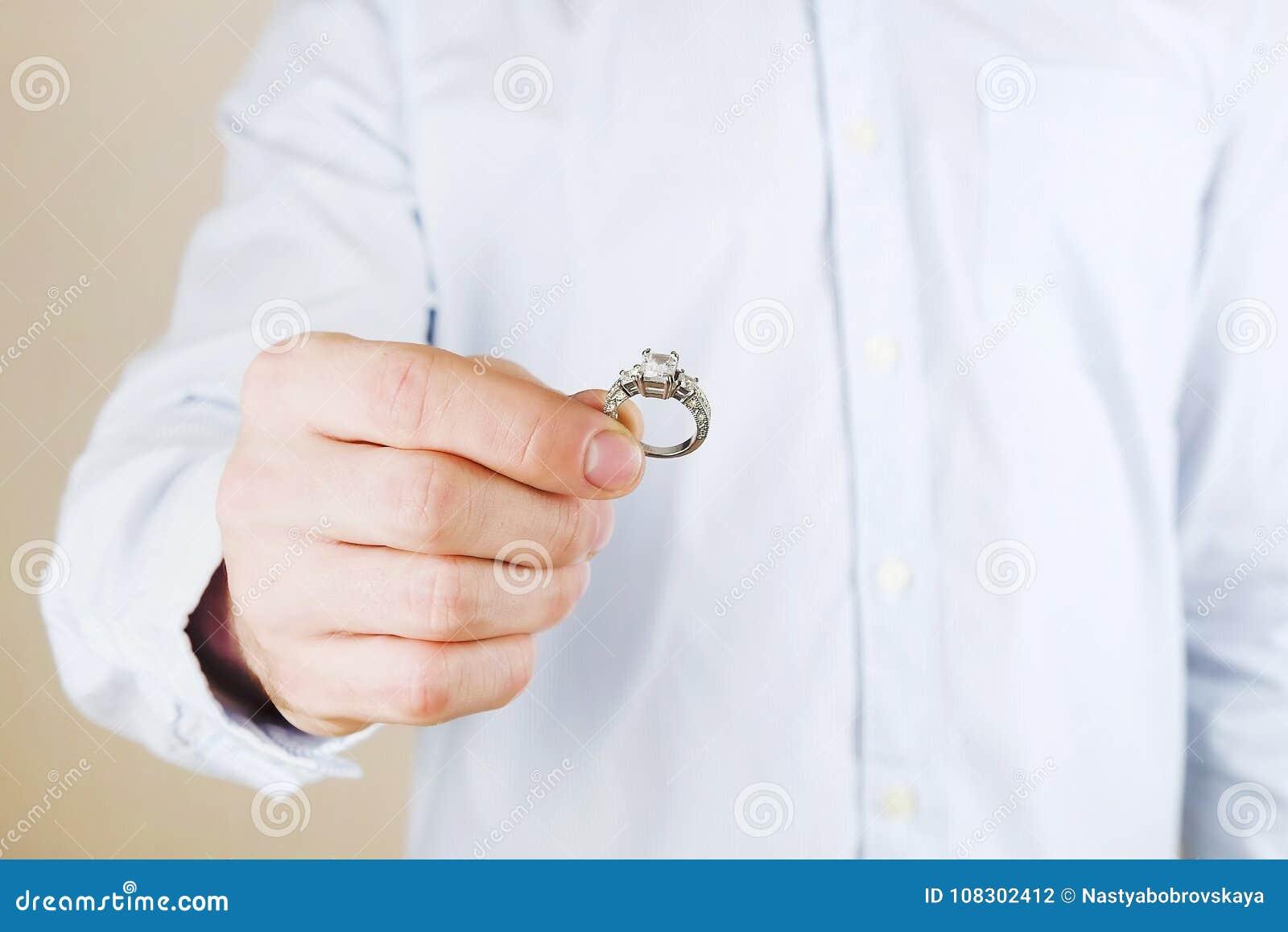 Verpflichtungs-/Heirat-/Heiratsantragszene Schließen Sie oben vom Mann, der seiner Braut den teuren Goldplatin-Diamantring übergi