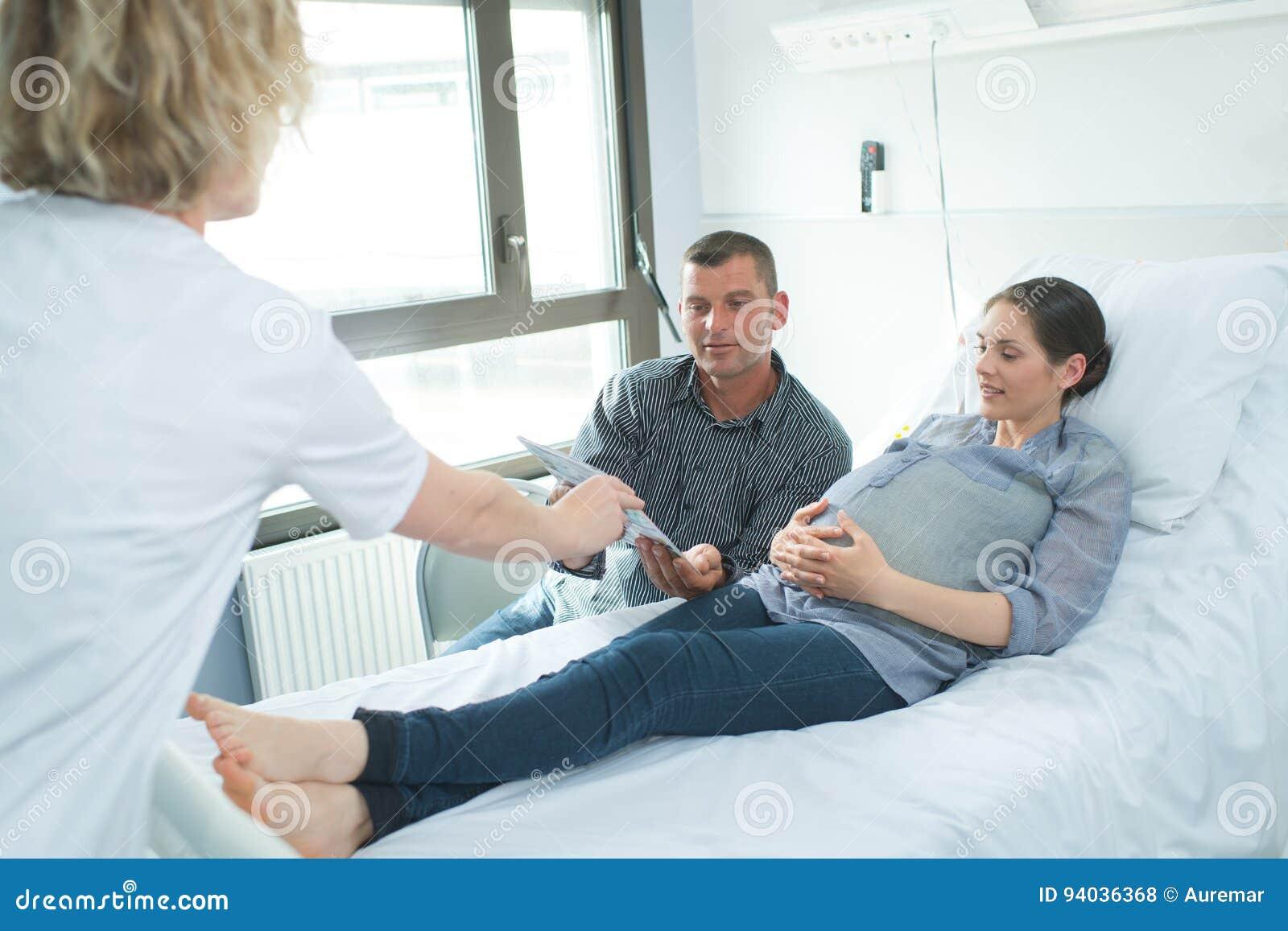 Verpleegster die document geven aan pregant vrouw en echtgenoot