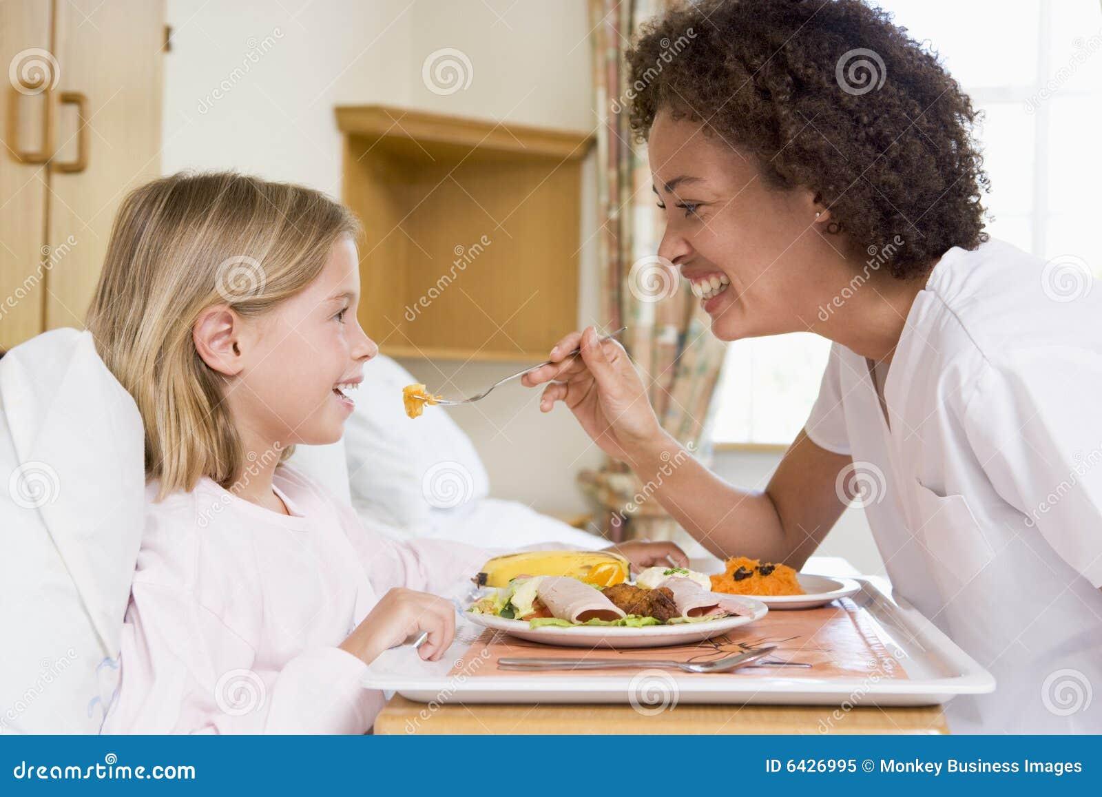 Verpleegster die Jong Meisje voedt