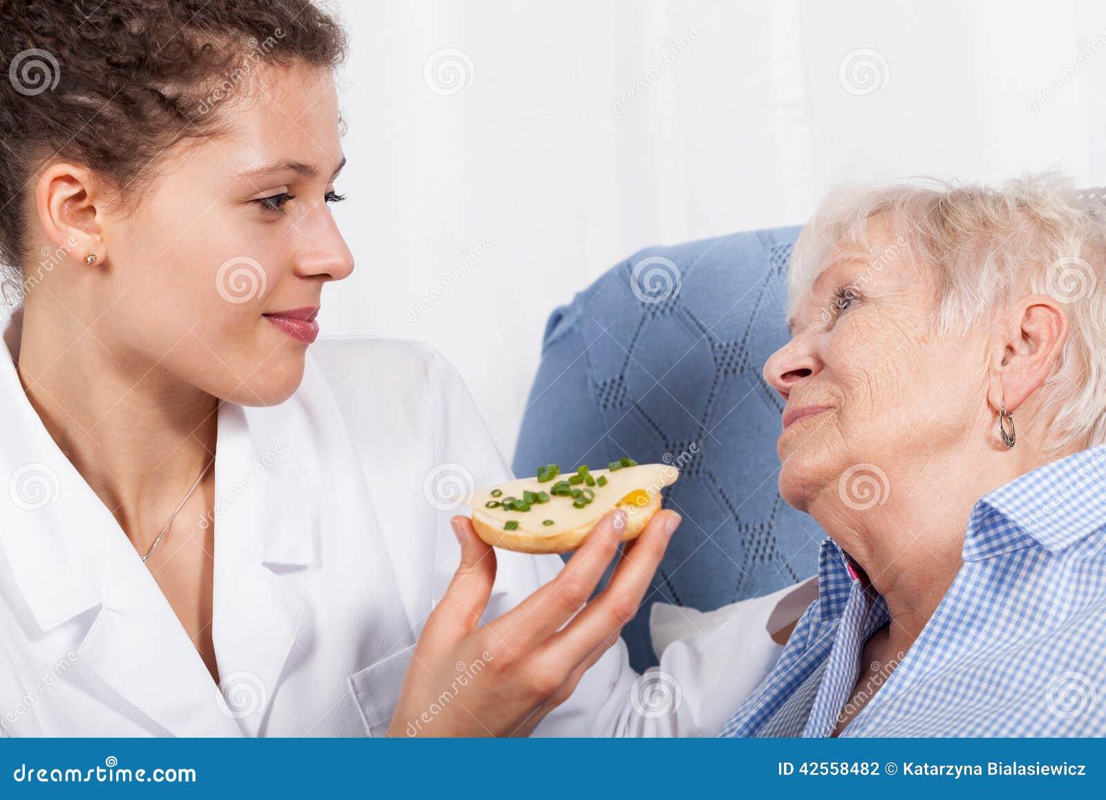 Verpleegsters voedend bejaarde