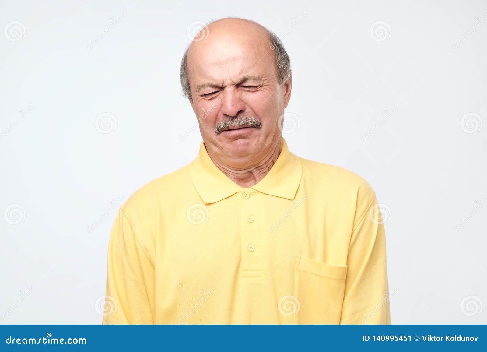 Verrückter älterer kahler hispanischer Mann, der schlechte Nachrichten empfangend schreit
