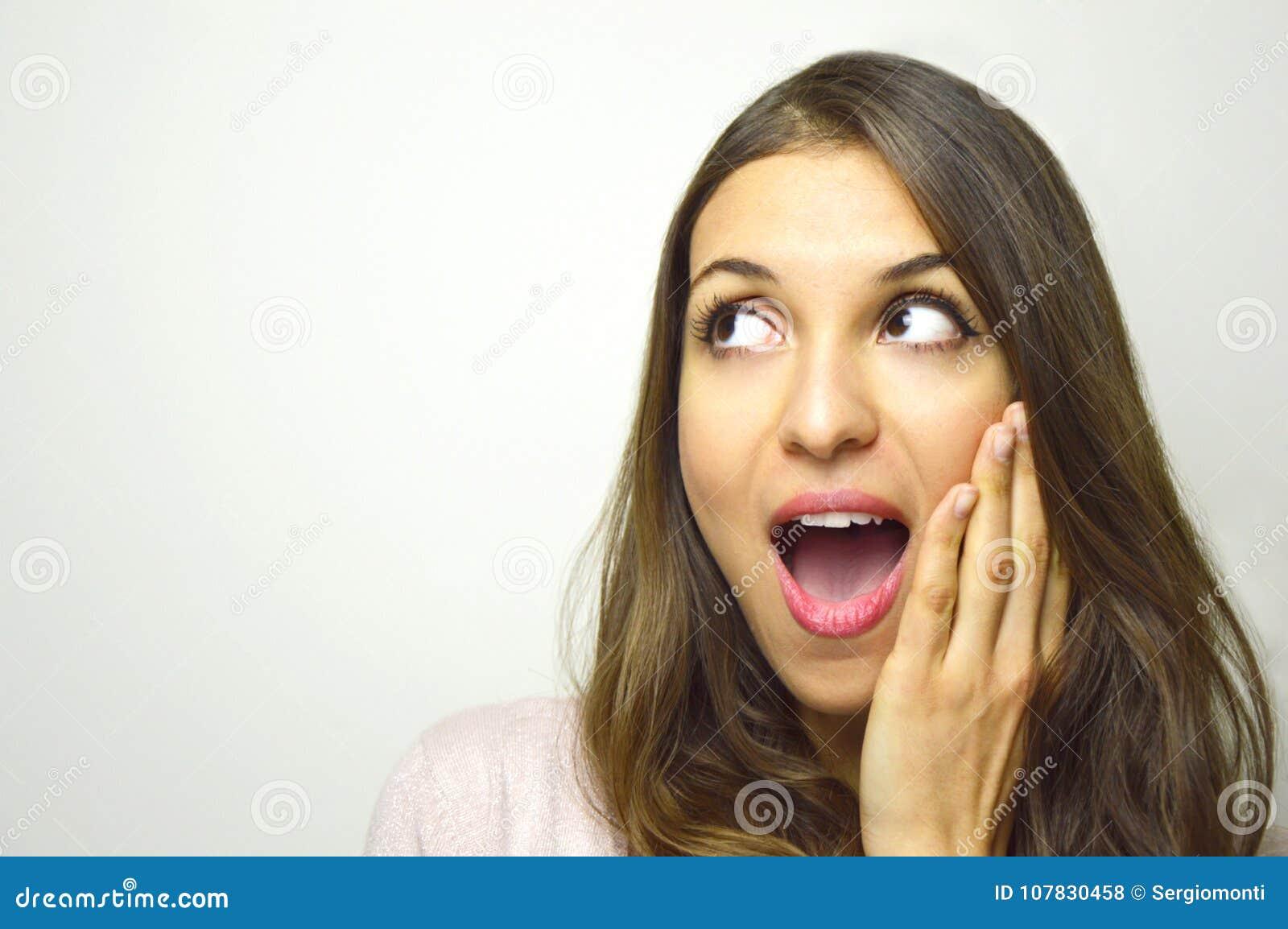 Verraste jonge vrouw die aan de kant met open mond met hand op het gezicht op witte achtergrond kijken Opgewekt meisje die aan s