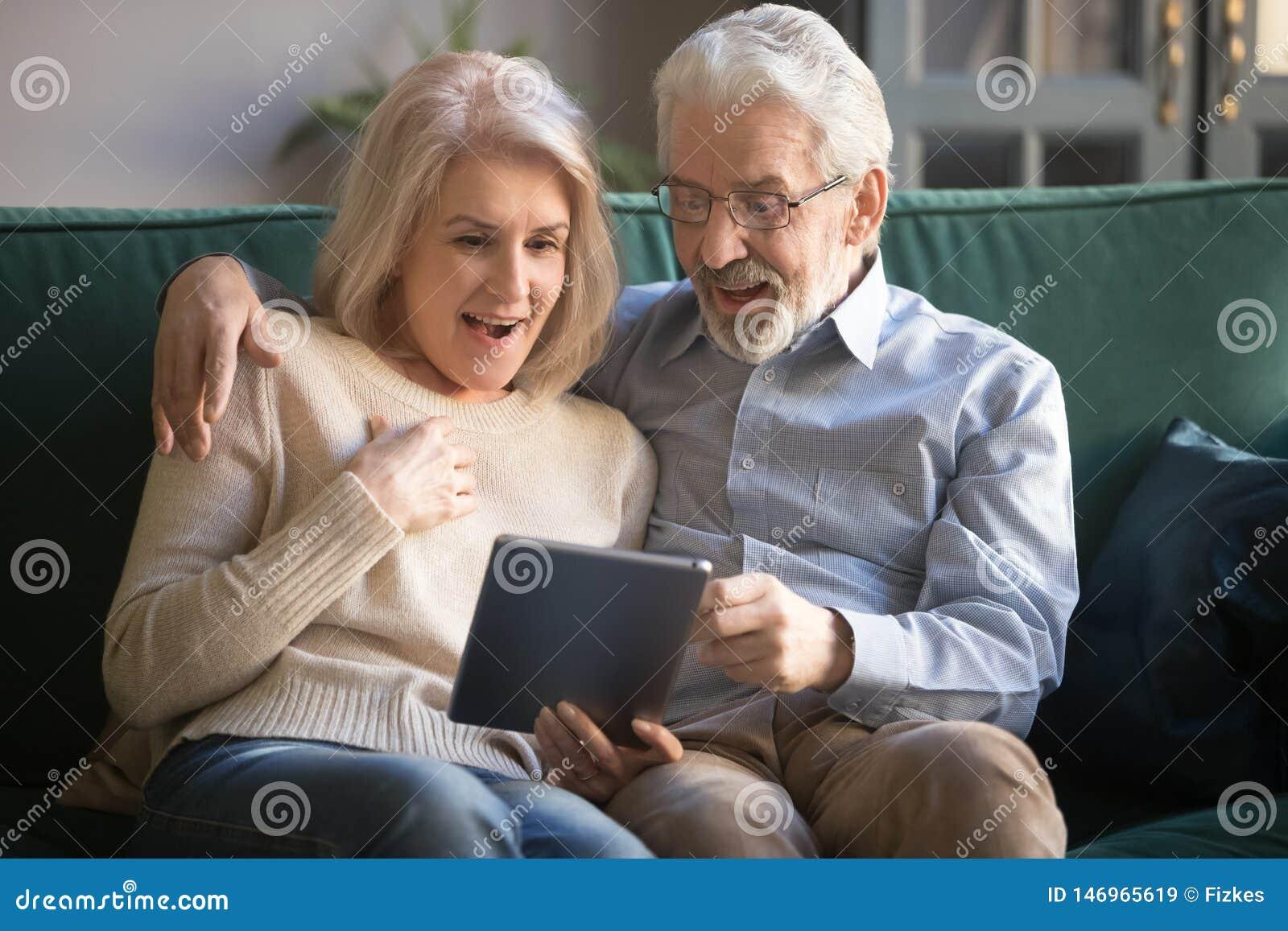 Verraste rijpe vrouw en echtgenoot die tablet gebruiken, die prettig nieuws lezen