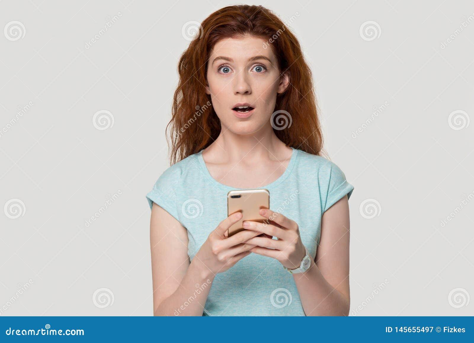 Verraste roodharigevrouw die door sms-bericht op cel wordt geschokt
