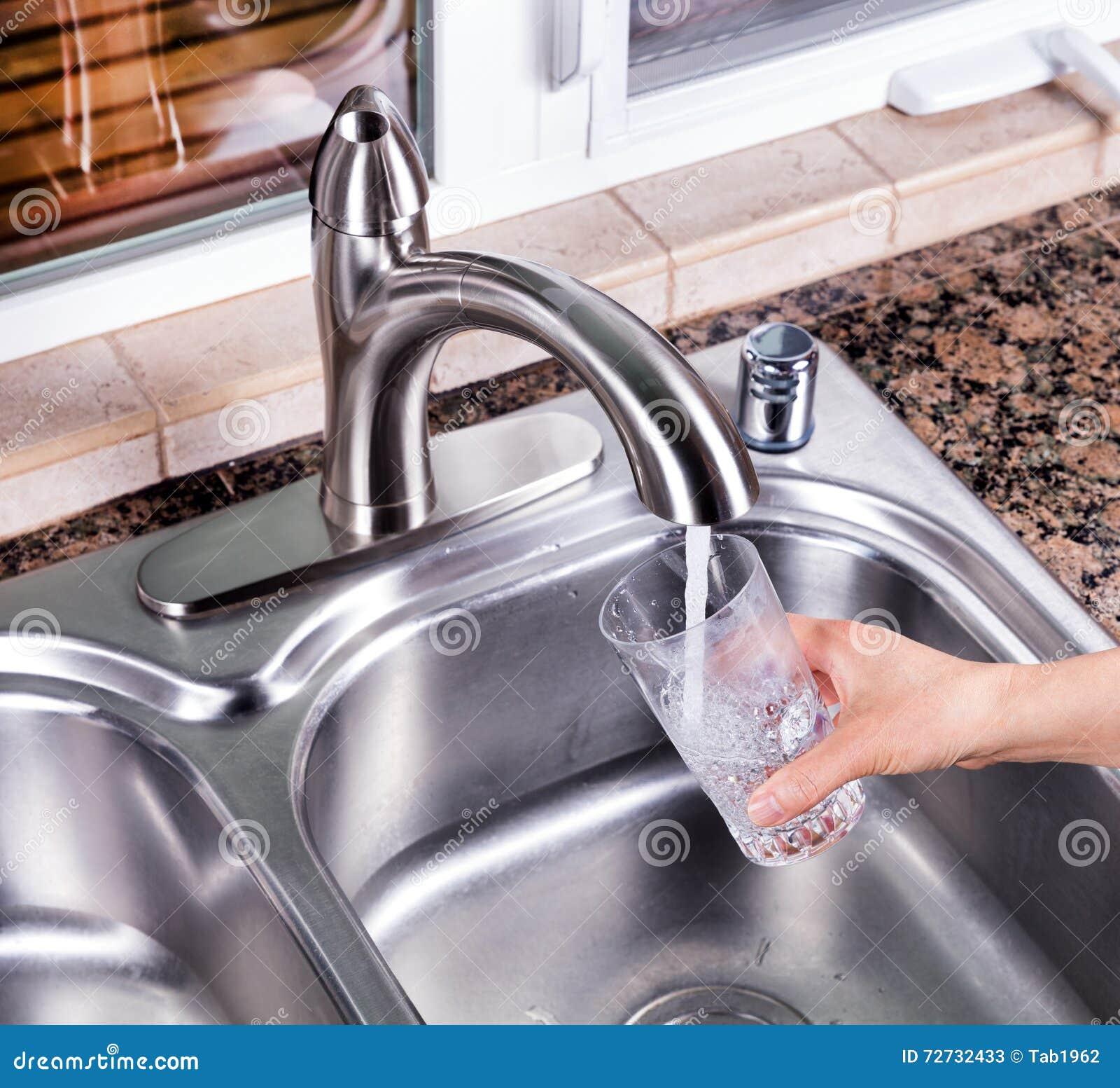 Verre à boire étant rempli avec de l eau l eau du robinet à partir du fauce de cuisine