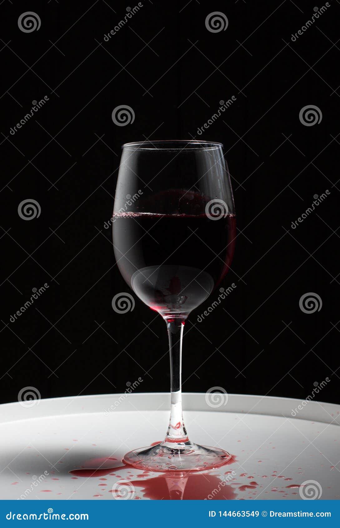 Verre à vin avec le vin rouge sur une table blanche