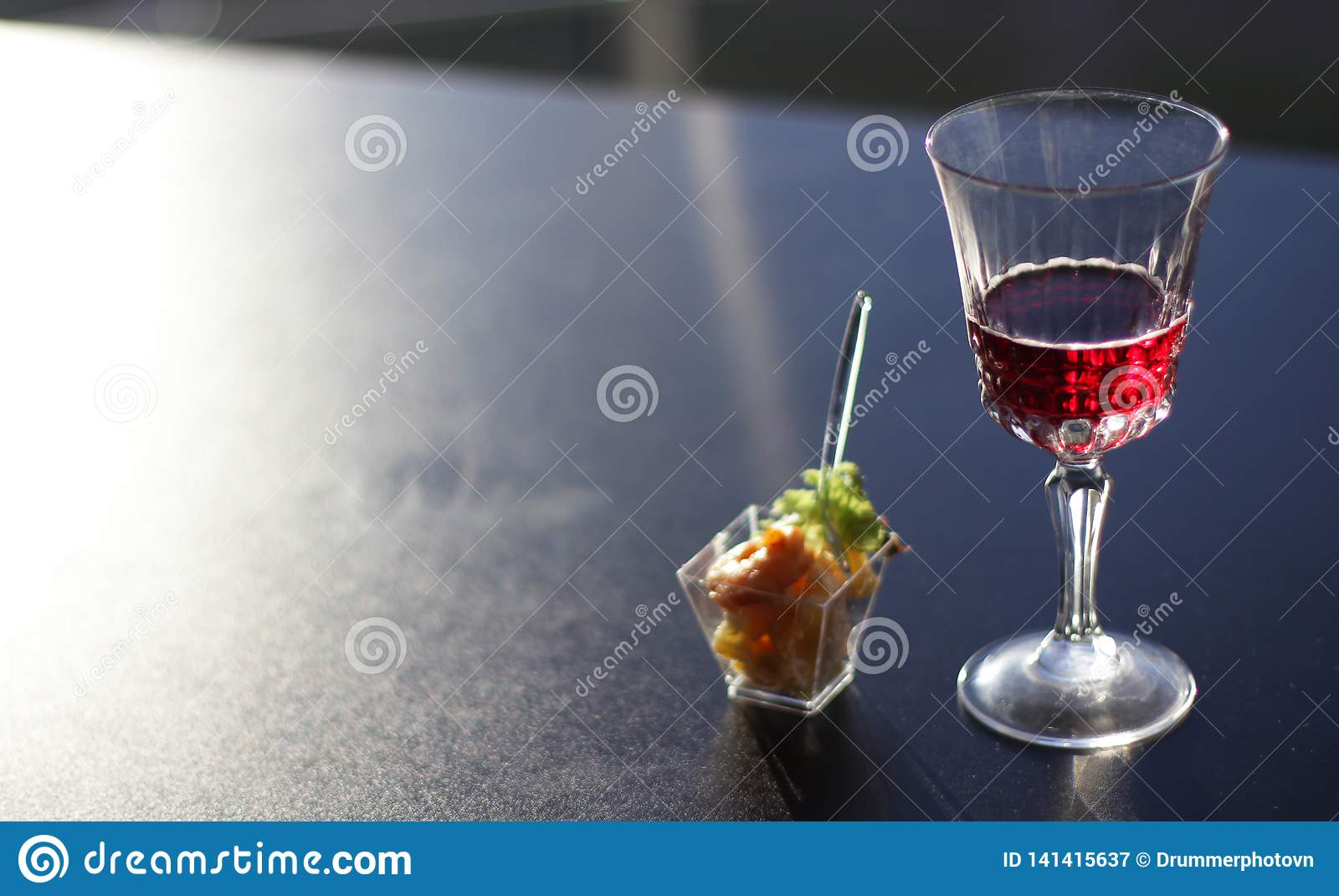 Verre avec du vin sur le dessus noir dans le bureau