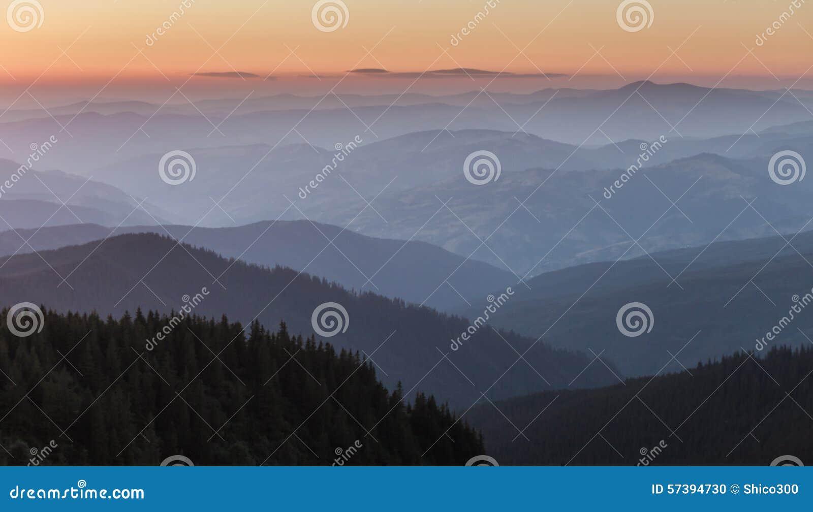 Verre bergketen en dunne laag wolken op de valleien