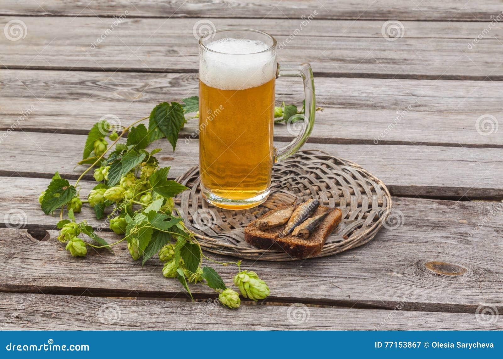 Verre de bière et de pain brun avec des esprots sur une table en bois