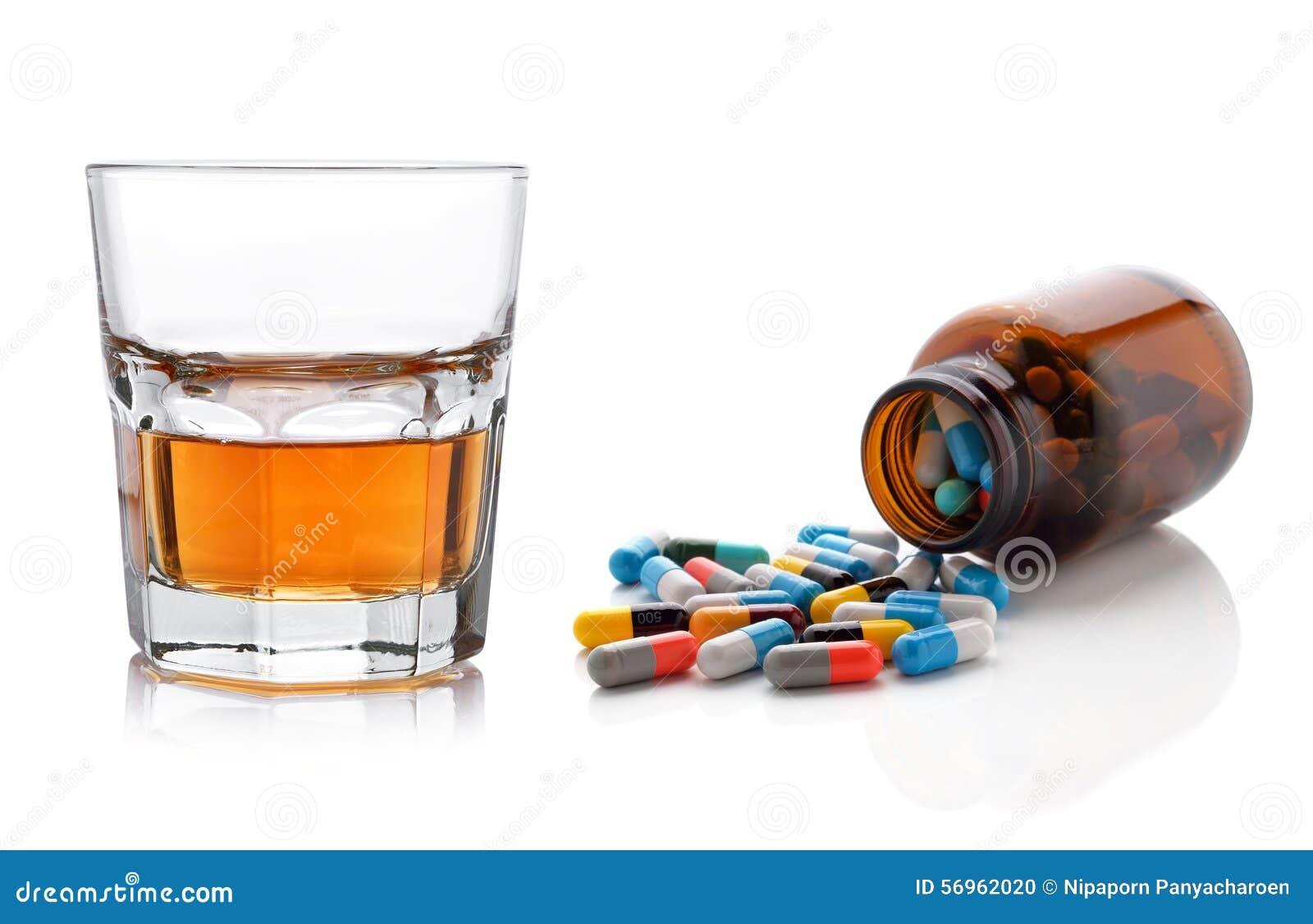 Verre de capsules de whiskey et de pilules