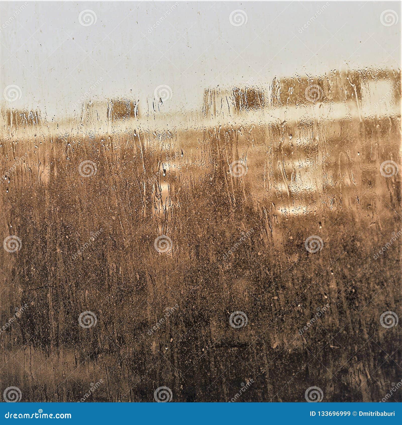 Verre de fenêtre avec les gouttes de pluie débordantes au-dessus de lui