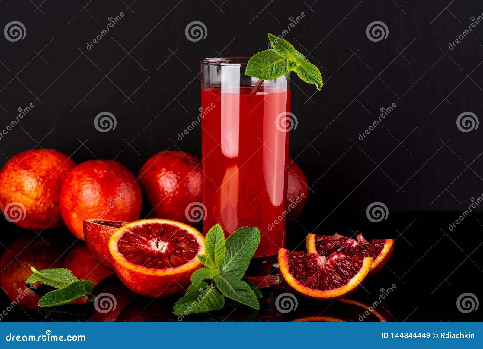 Verre de jus avec des quelques morceaux d orange sicilienne sur un fond noir Orangeade sicilienne