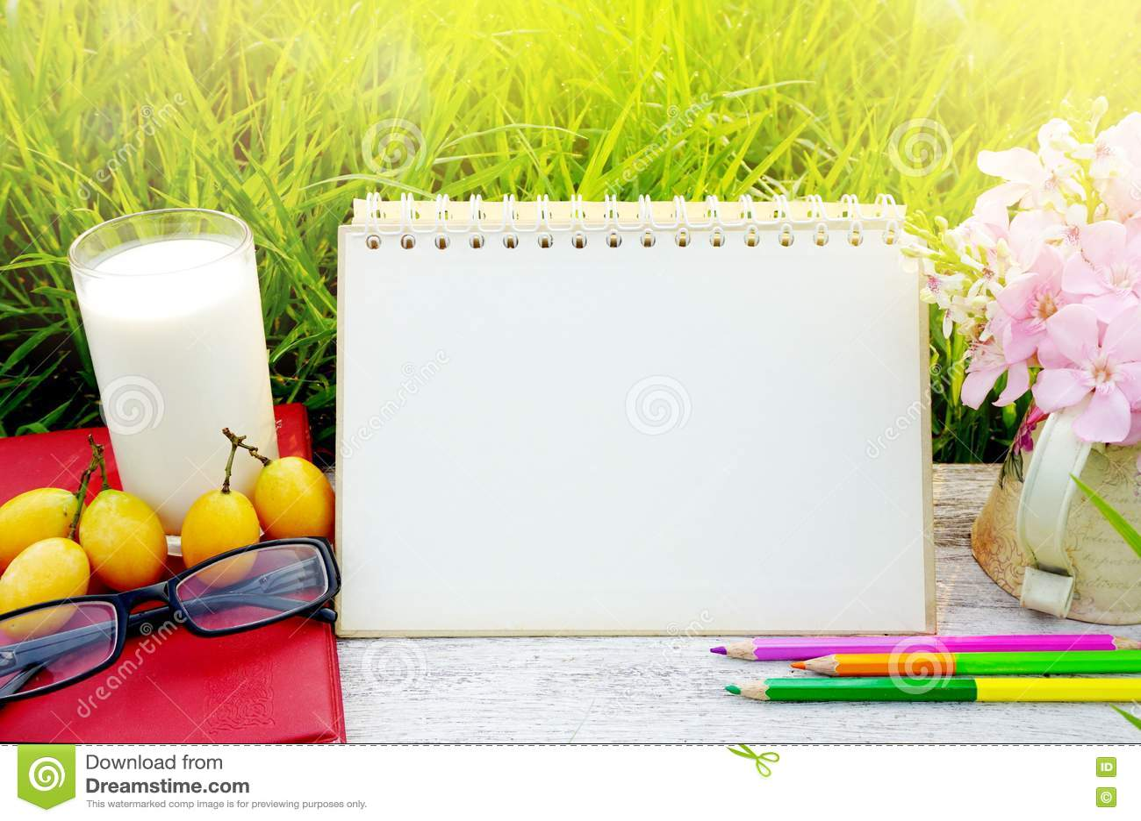 Verre de lait, de calendrier de page vide, de fruit jaune, de lunettes de soleil, de crayons et de fleur rose sur la table en boi