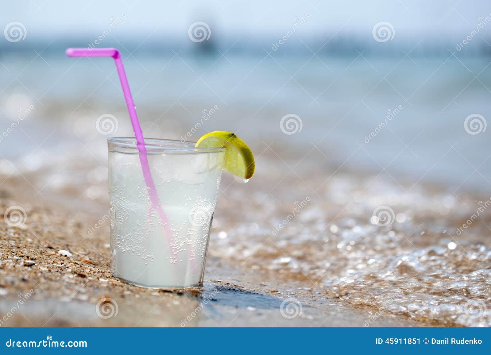 verre de limonade ou d 39 eau sur la plage par la mer image stock image du fruit glace 45911851. Black Bedroom Furniture Sets. Home Design Ideas