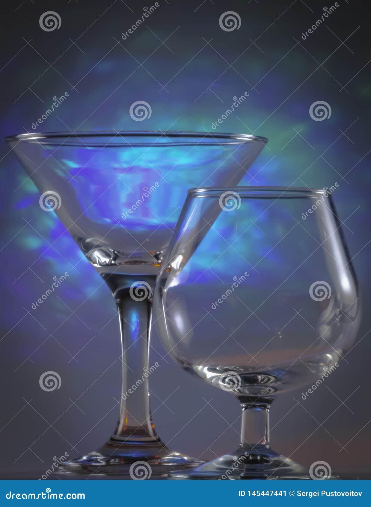 Verre de Martini ainsi que le verre de cognac avec les lumi?res bleues lumineuses de clignotant sur le fond