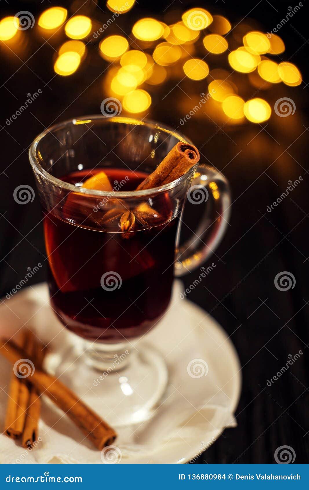 Verre de plan rapproché de vin chaud avec l orange et la cannelle sur le fond noir foncé, du plat blanc, lumières de Noël, grand