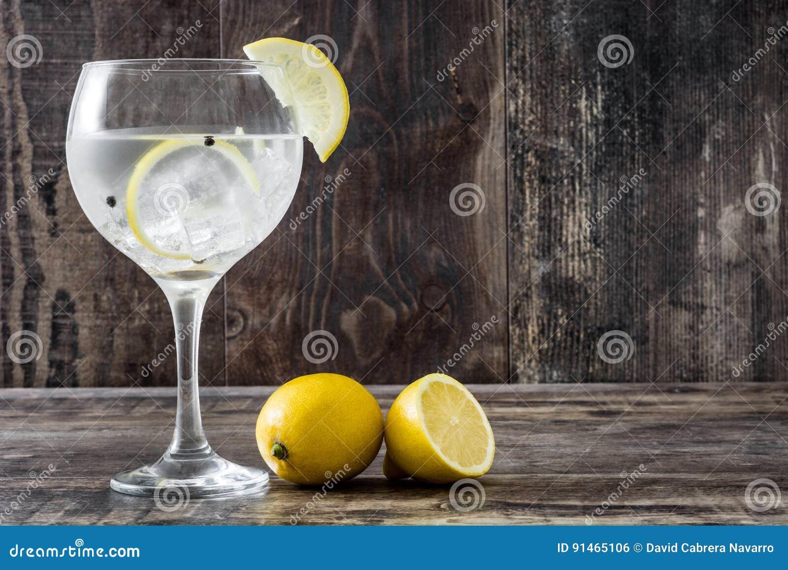 Verre de tonique de genièvre avec le citron sur le bois