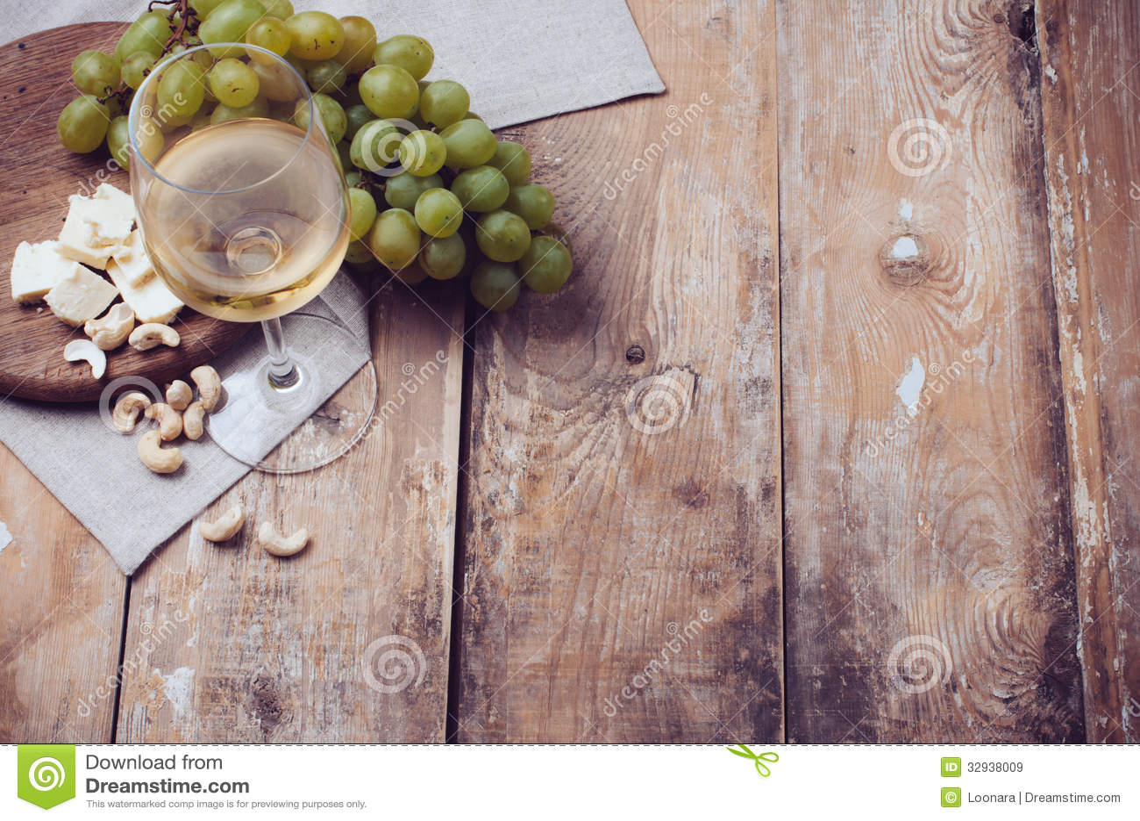 Verre de vin blanc, de raisins, de noix de cajou et de fromage à pâte molle