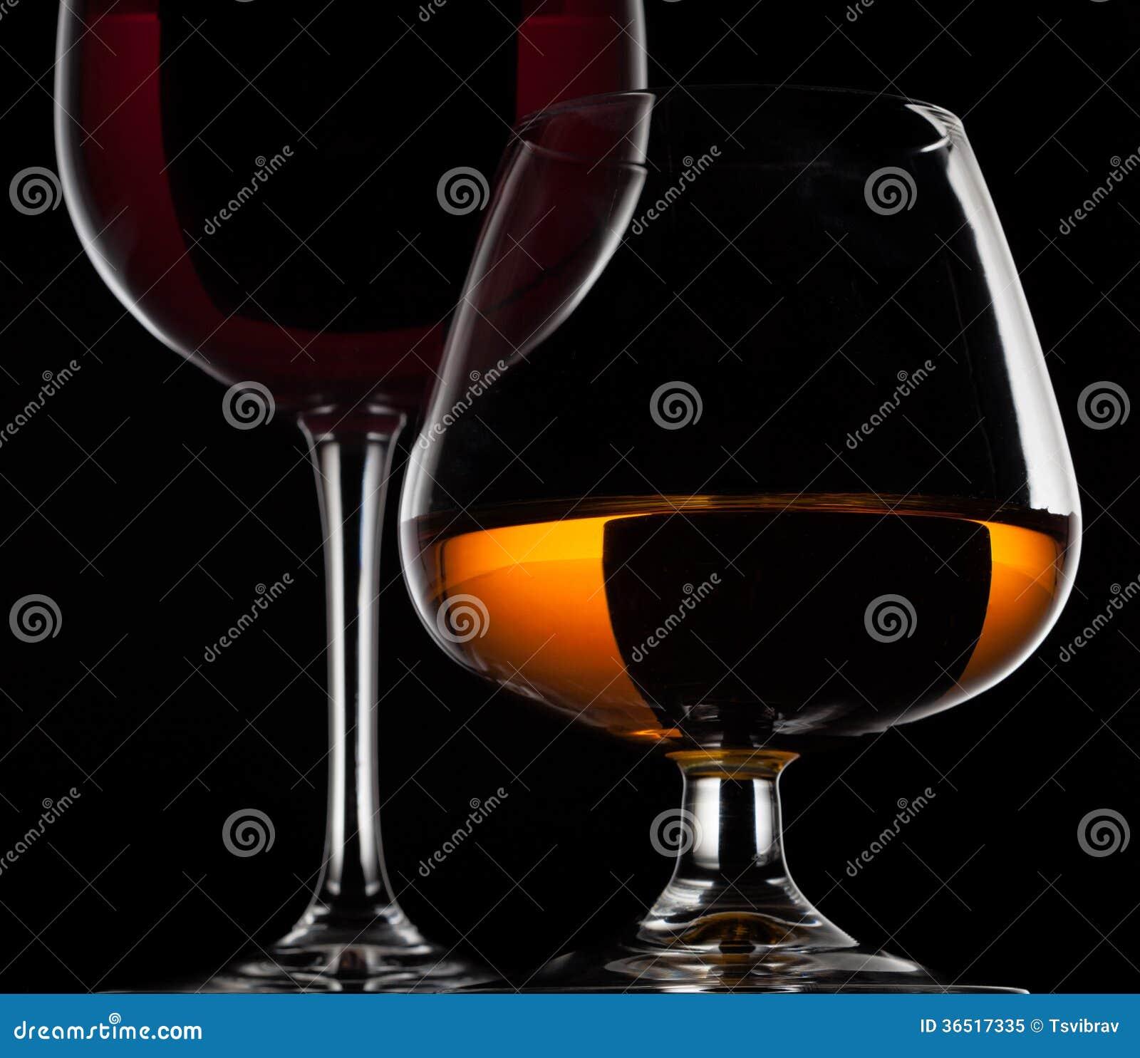 Verre de vin et verre de whiskey sur le fond noir