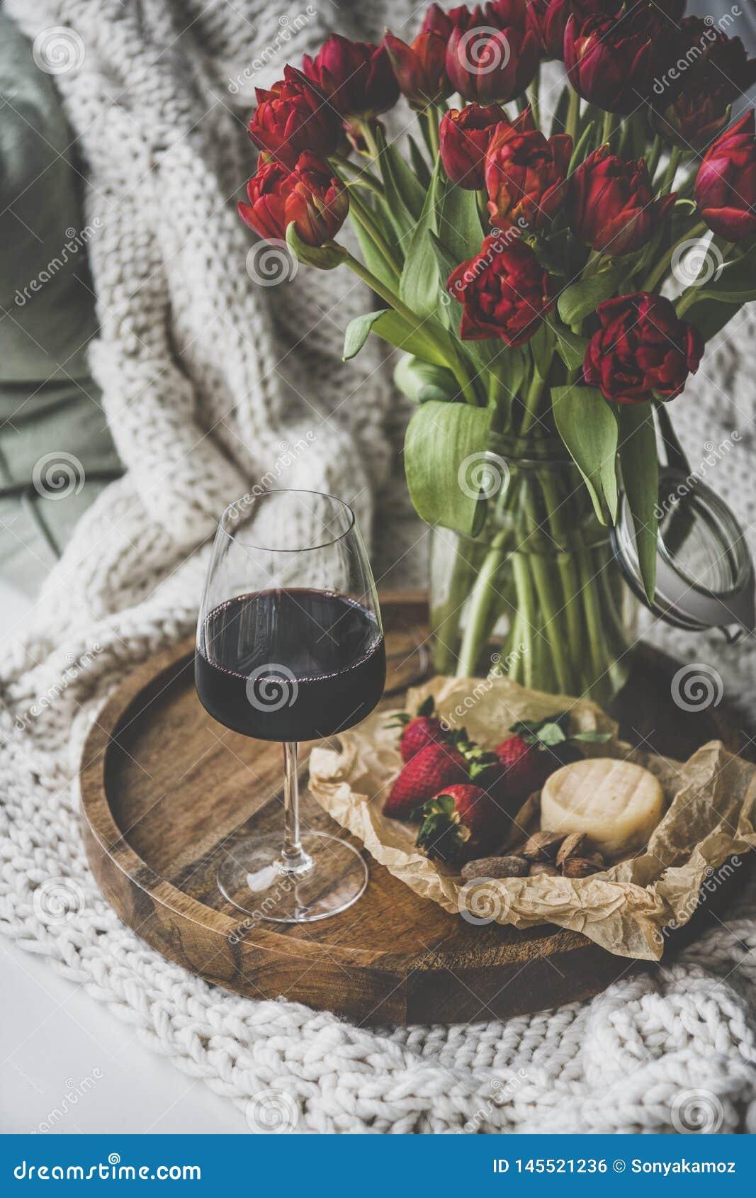 Verre de vin rouge, de casse-cro?te et de tulipes au-dessus de couverture tricot