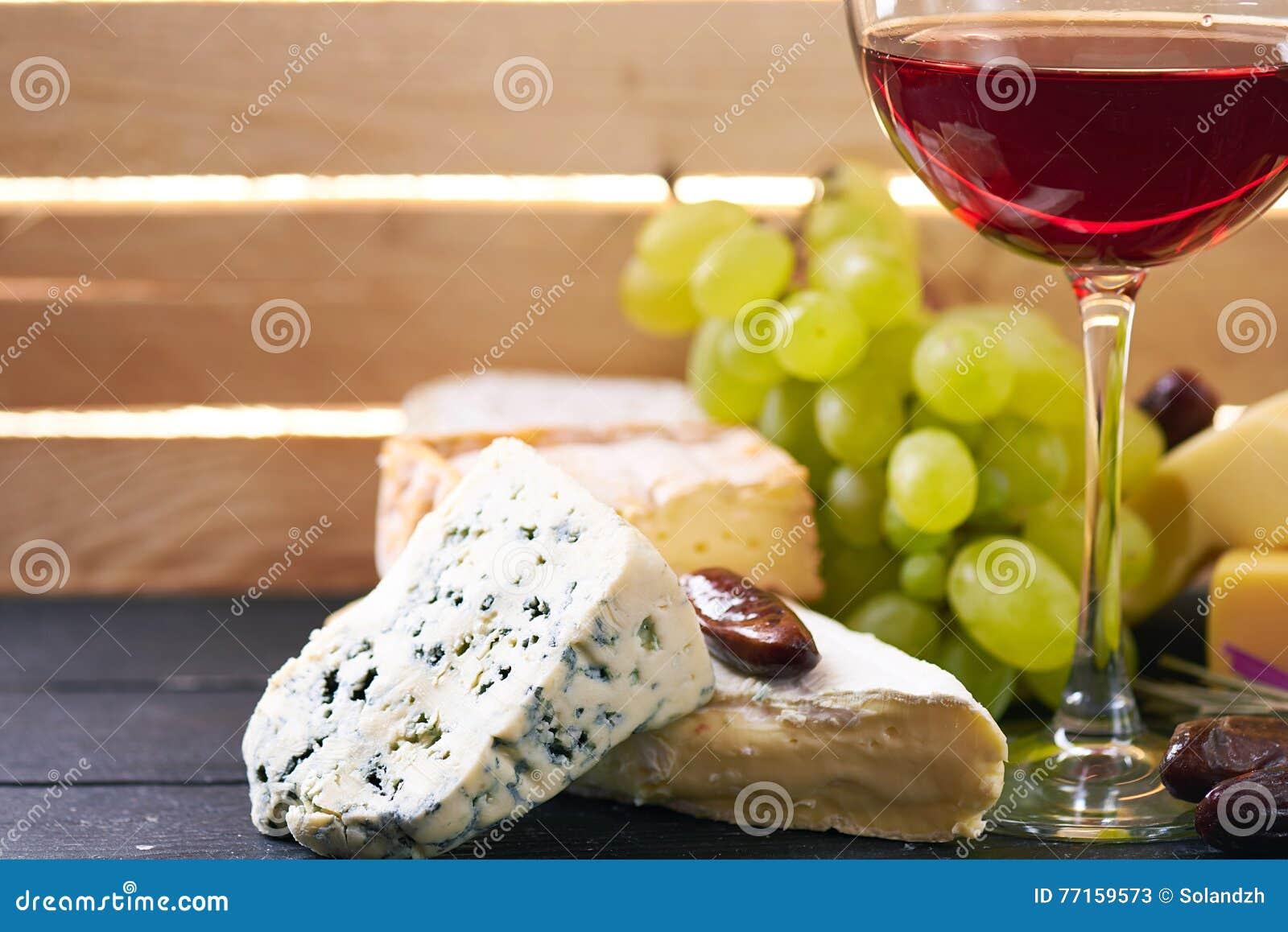 Verre de vin rouge, servi avec des raisins et le fromage