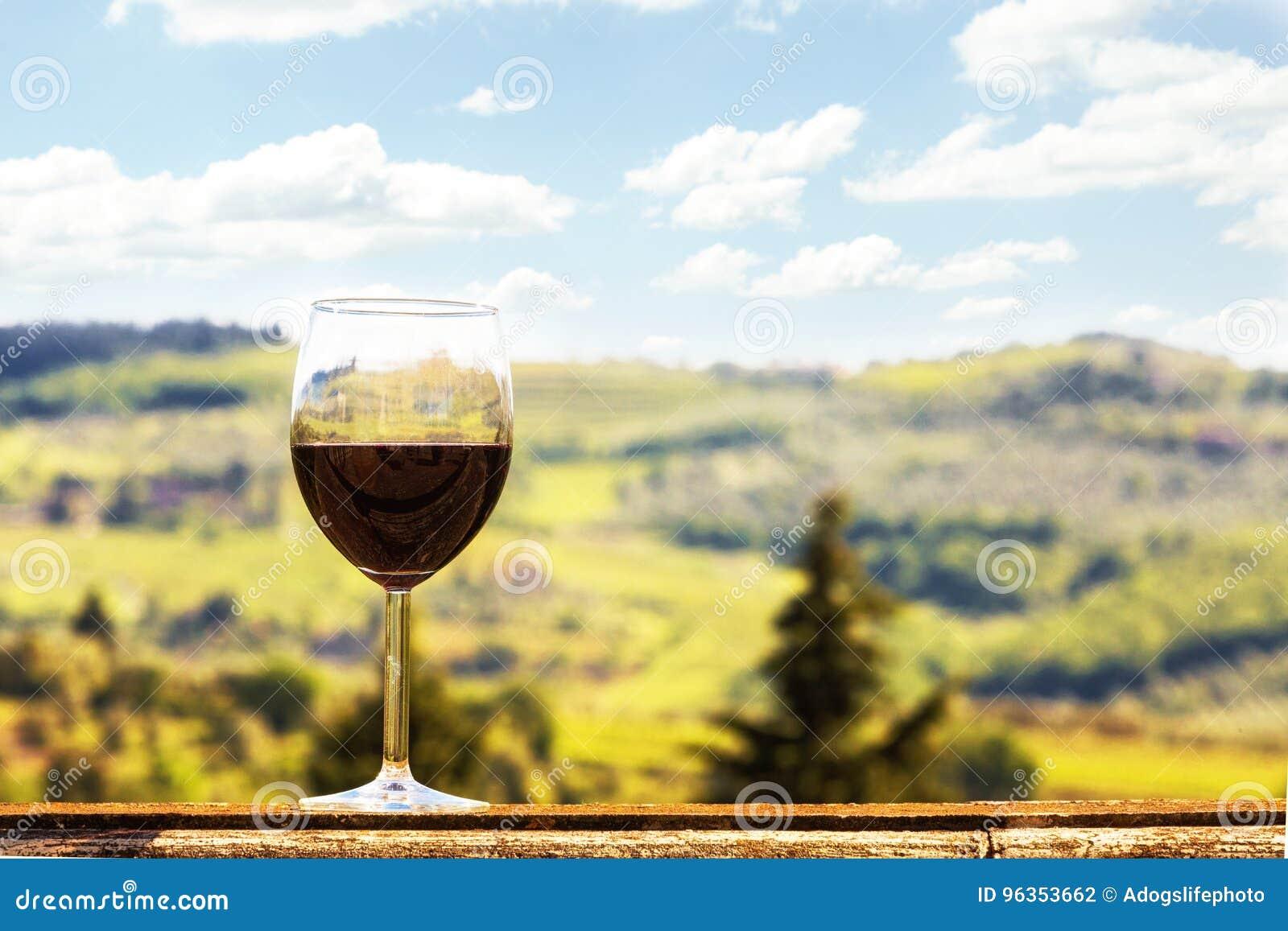 Verre de vin sur Ledge Overlooking Vineyards dans le chianti Italie