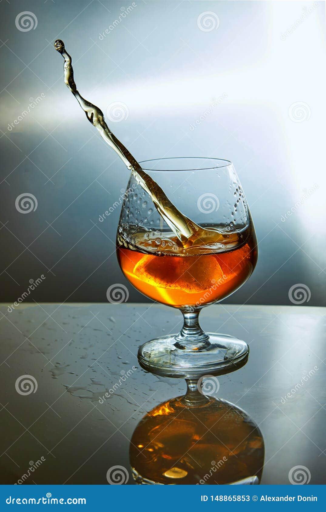 Verre de whiskey avec une vague sur un fond bleu