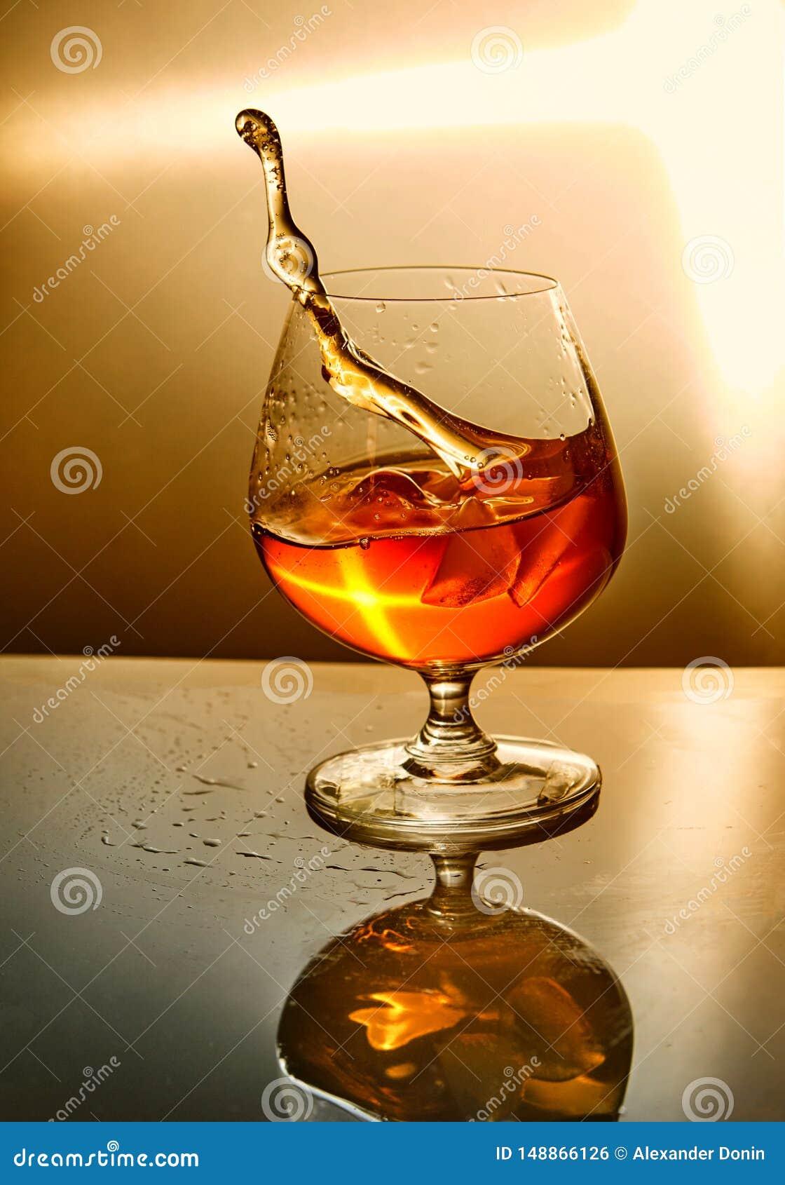 Verre de whiskey avec une vague sur un fond orange