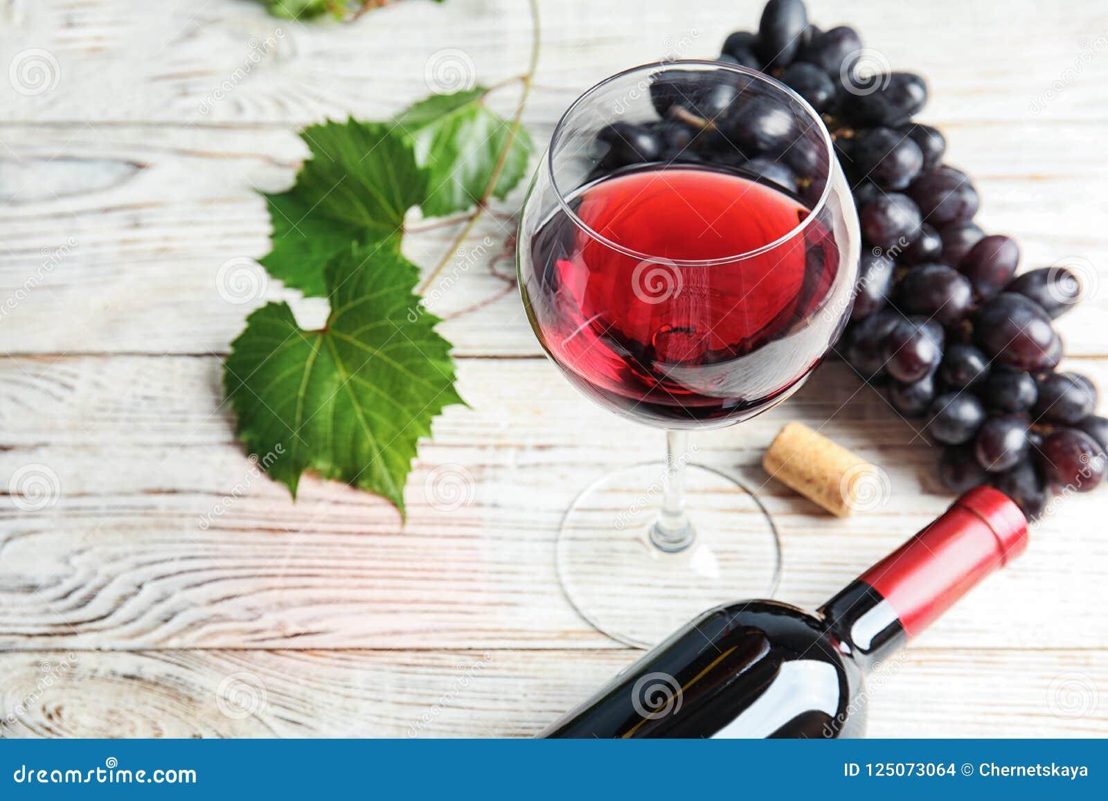 Verre et bouteille de vin rouge avec des raisins juteux mûrs frais