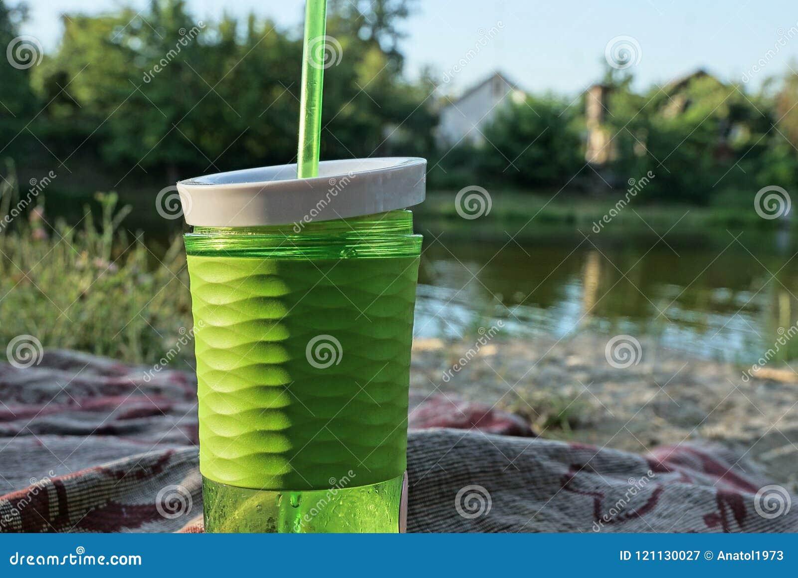 Verre vert en plastique avec une boisson et un tube sur la plage près de l eau