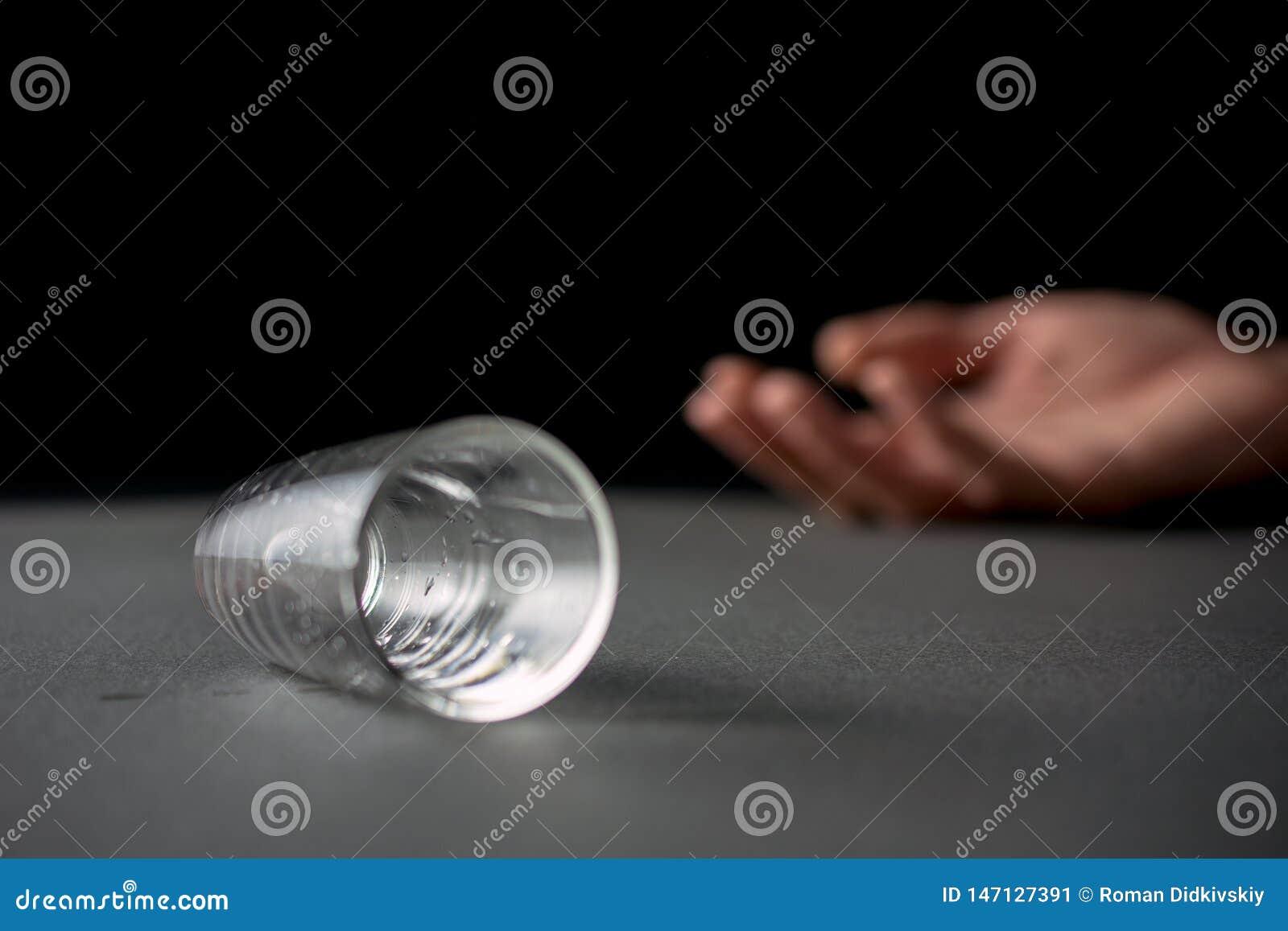 Verre vide menteur bu par main de vodka ou de boisson alcoolis?e