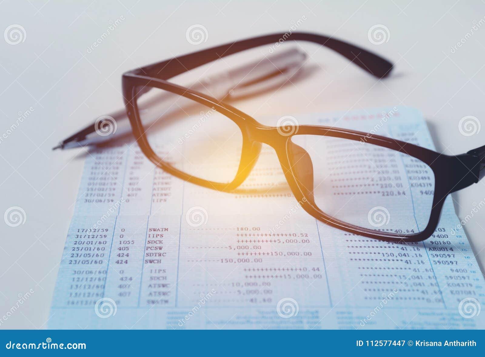 Verres avec le carnet de compte bancaire pour l épargne financière et le CRNA