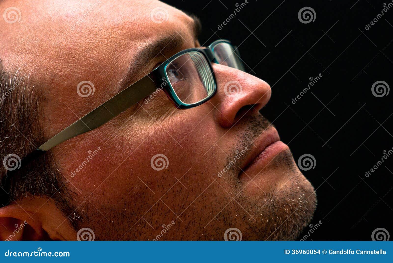 Verres de port d homme caucasien barbu recherchant sur le noir