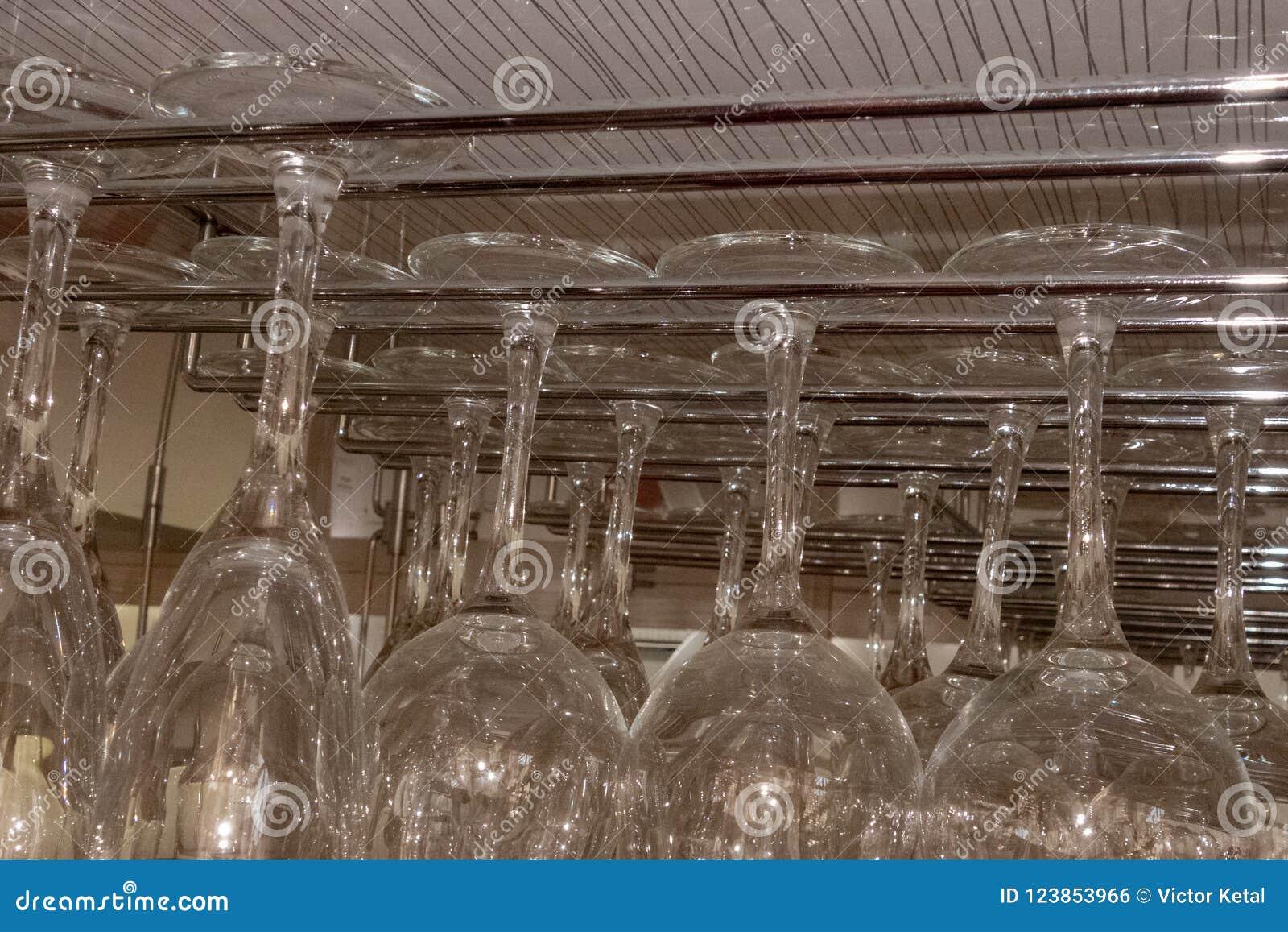 Verres en verre accrochés de la barre Des gobelets en verre sont suspendus des guides en métal dans la barre