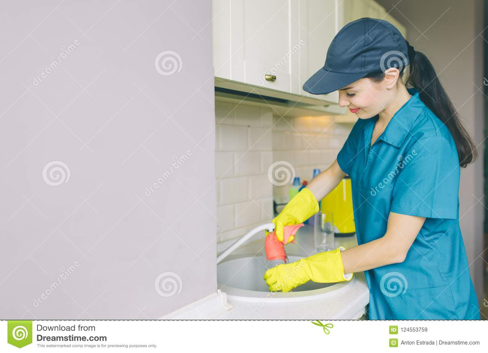 Verrukkelijk meisje in GLB en eenvormige tribunes en de werken bij gootsteen Zij glimlacht een beetje Het meisje is professionele