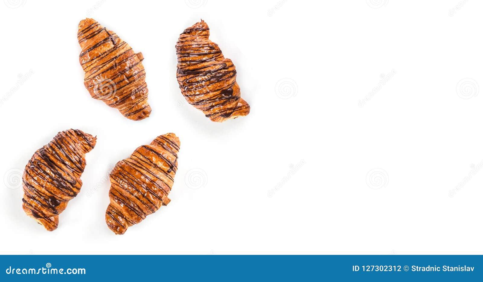 Vers gebakken die croissants met chocoladesaus worden verfraaid op witte achtergrond, hoogste mening wordt geïsoleerd
