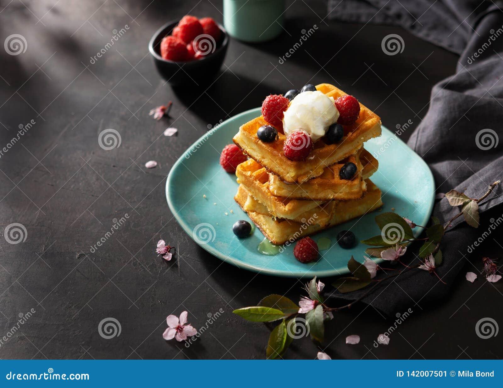 Vers gebakken wafels met frambozen, bessen, honing en koffie voor ontbijt of brunch op een donkere achtergrond met exemplaarruimt